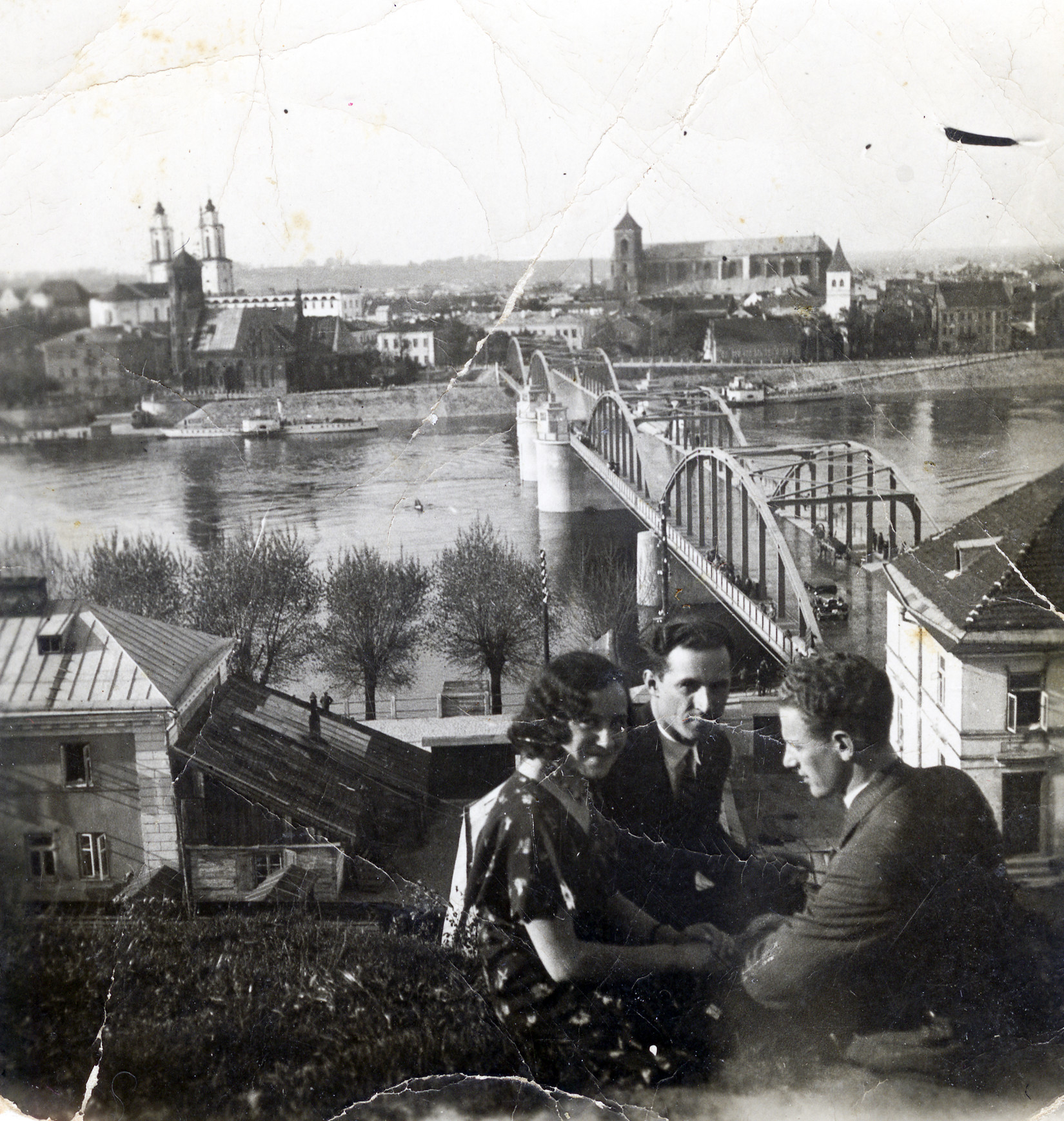 Lithuanian Jewish siblings seated together, overlooking a river in Kovno.  Pictured are Genia Kopelanski and her two brothers, Yaakov and Leib.