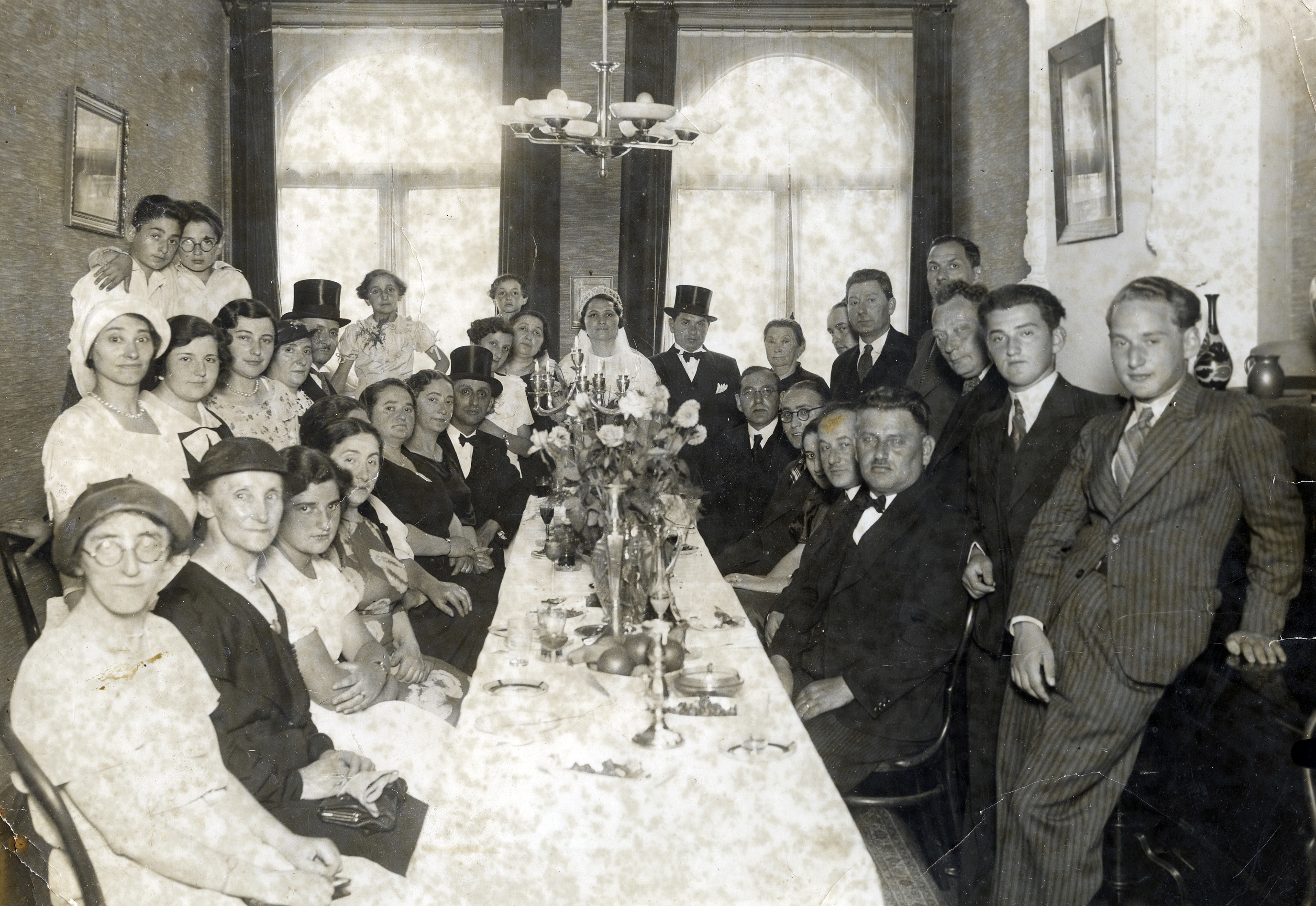 A Dutch Jewish family celebrates a wedding.  Pictured at the end of the table are the bride and groom, Shela (Shifra) Thaler Erlich and Mr. Erlich.  In the left back, wearing a top hat, is Isaac Stopper.