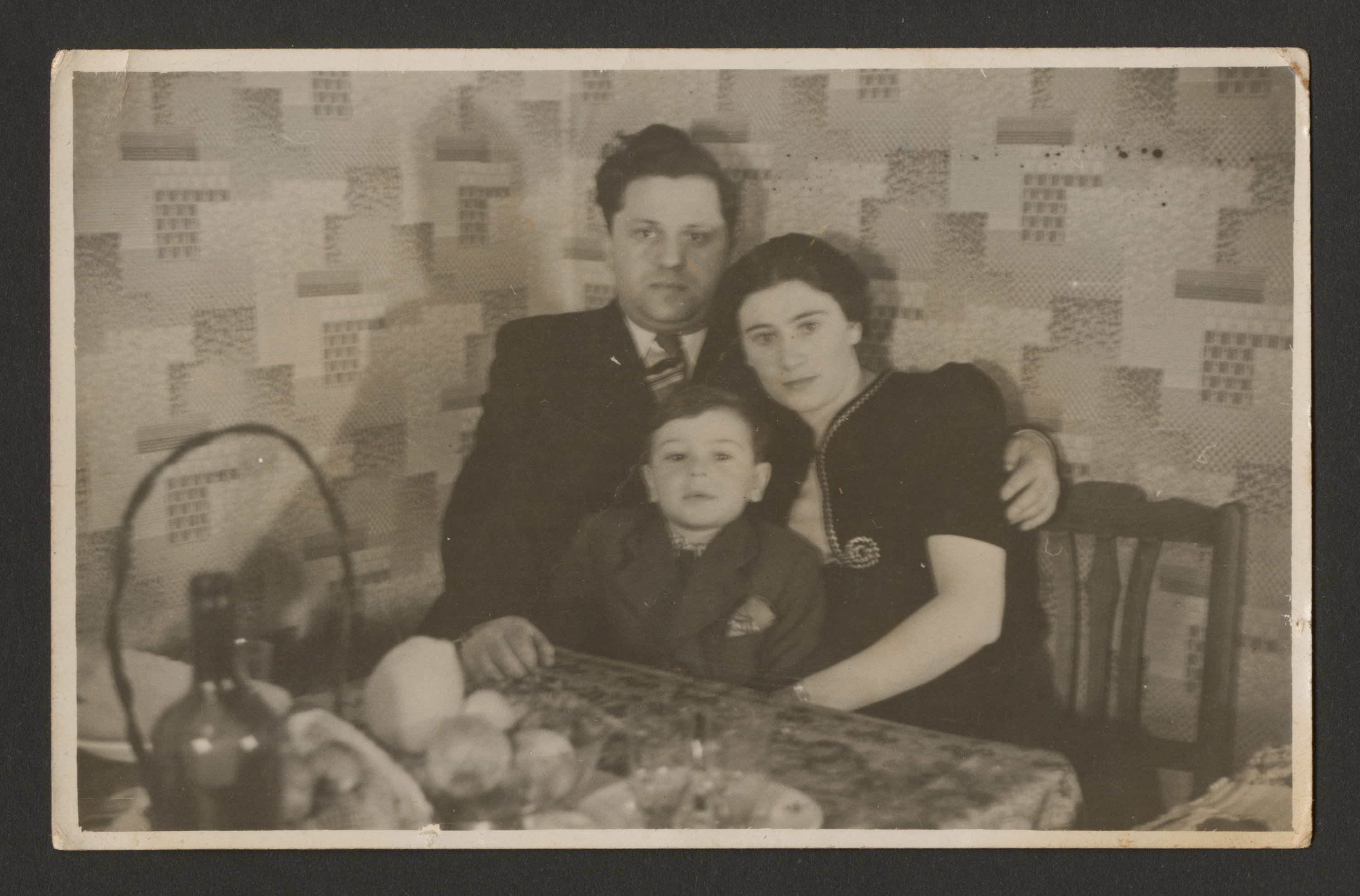 A Belgian Jewish family sits together at a dining tabe.  Pictured are Leon and Maria Srebnik, with their son Charles.