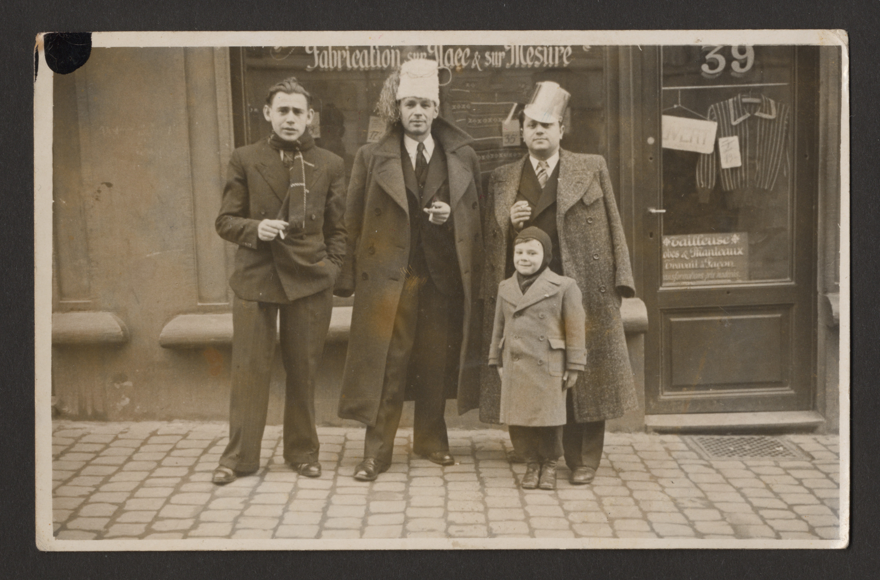 A Jewish father and son stand in front of the family store with two companions.  Among those pictured is five-year-old Charles Srebnik, with his father Leon Srebnik standing directly behind him.  Charles is wearing boots with hollow heels which his father had made for him and his mother,  as a hiding place for jewelry.    The other two men have not been identified.
