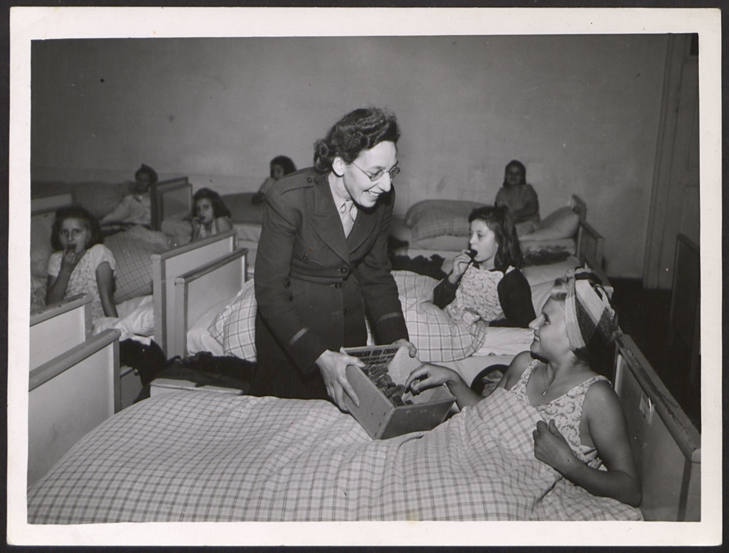 The director of the Kloster Indersdorf DP children's center  Lillian Robbins distributes chocolate to DP girls.