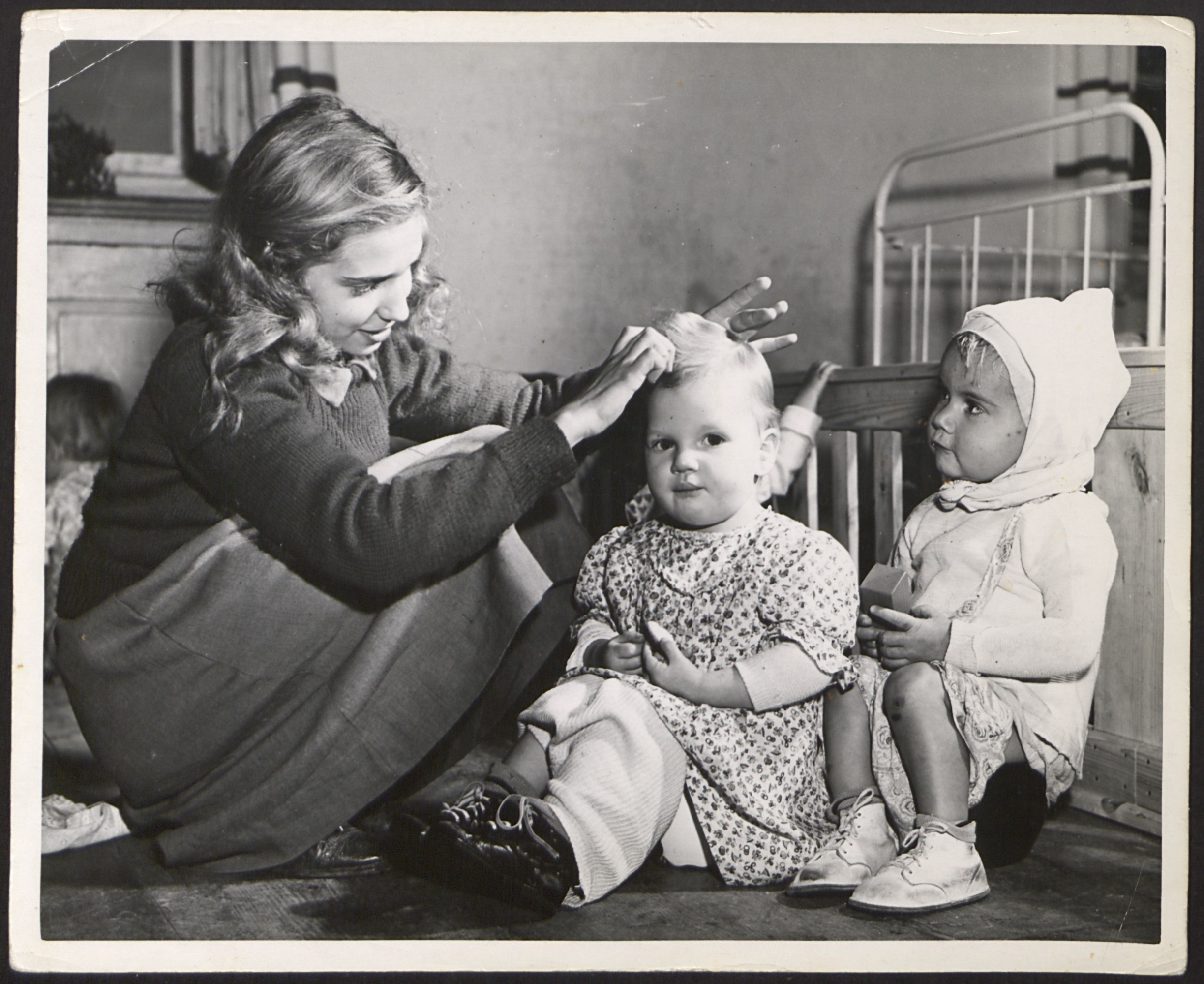 An older girl combs the hair of an infant at the Kloster Indersdorf children's DP center.