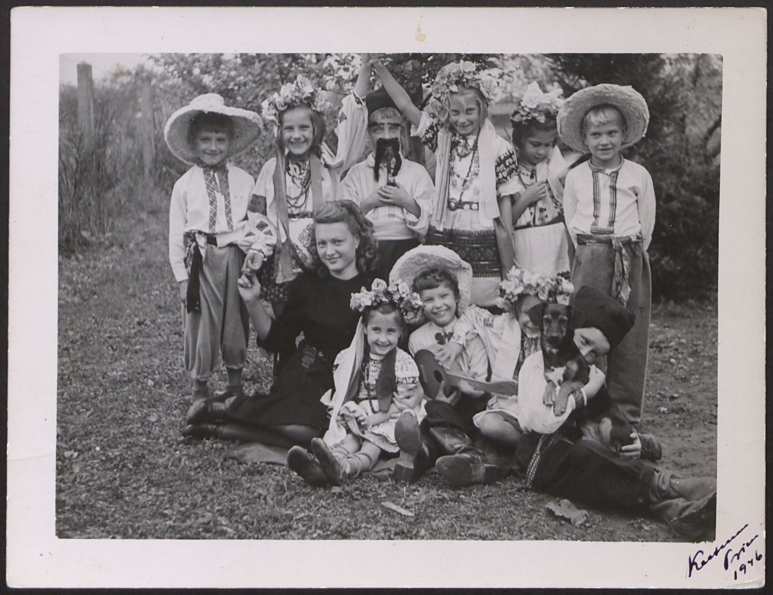 DP children dress in costume at the Prien am Chiemsee DP children's center.   Seated, wearing a black dress is Elena (Kobylska) Wyshnevsky, a teacher with the UNRRA Team 182.  Dominika Myskiw is standing second from left in the back row.
