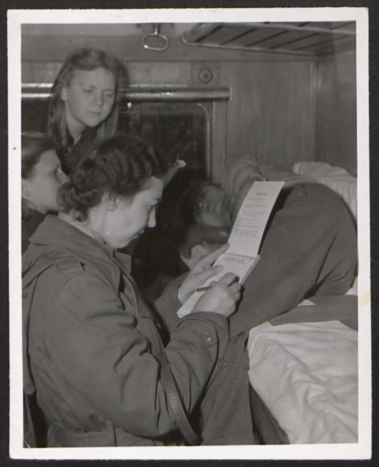 UNNRA relief worker, Greta Fischer, interviews a teenage boy, who is lying in a bunk on a Red Cross train.