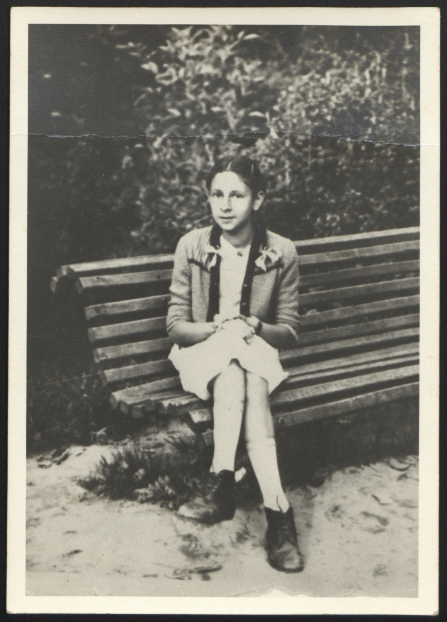 Portrait of Dawid Tennenbaum sitting on a park bench while living in hiding disguised as a girl.