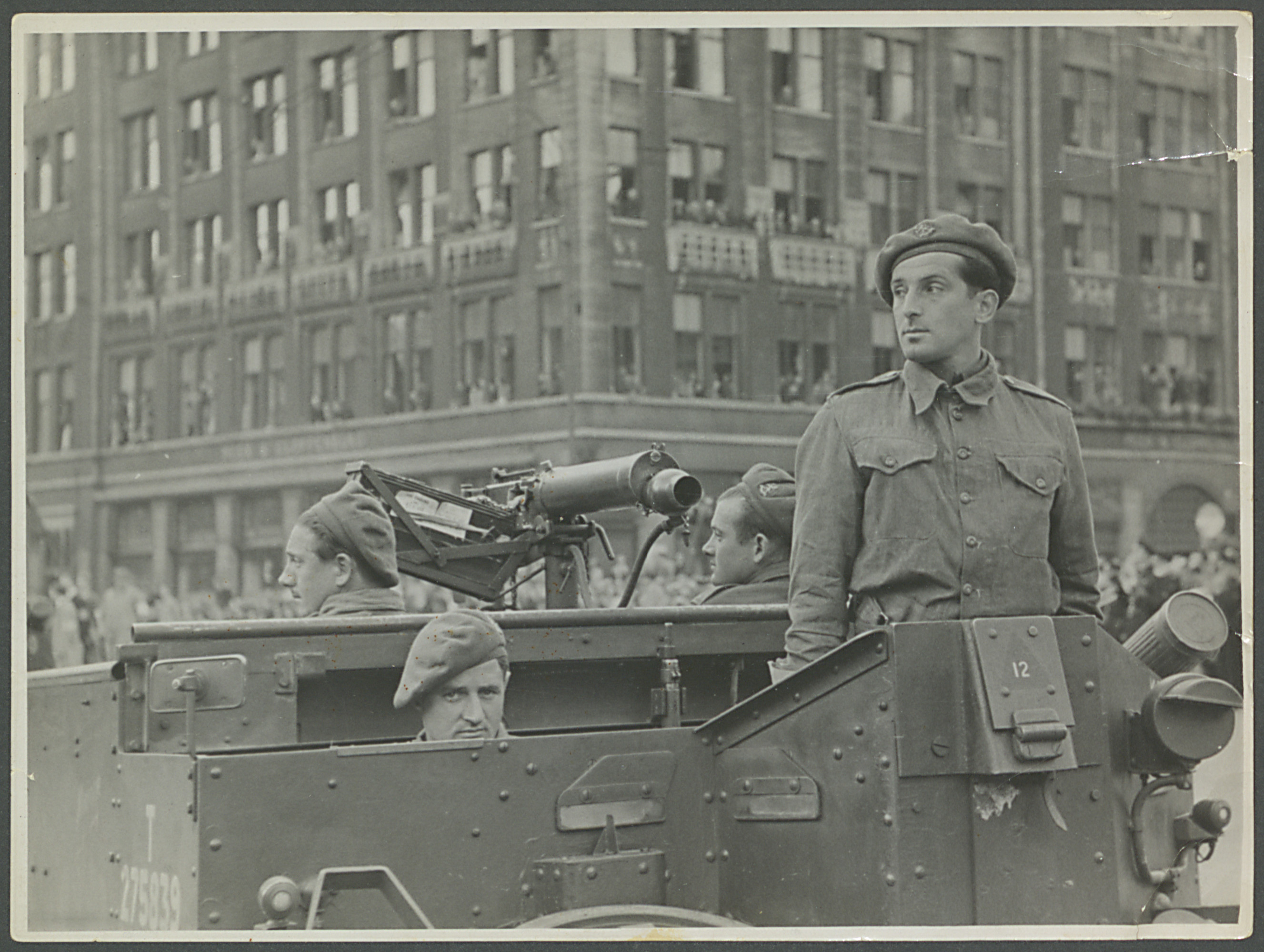 Jacques Grootkerk and members of the Princess Irene Brigade of Dutch Free Forces rides in a military vehicle in the liberation parade in Amsterdam.