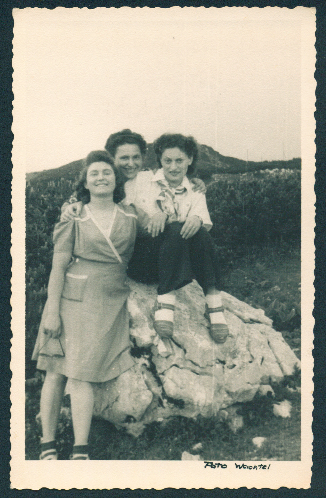 Three Jewish women pose on a large rock in a field near the Bindermichl displaced persons camp.  Ada Breitkopf is pictured on the left.