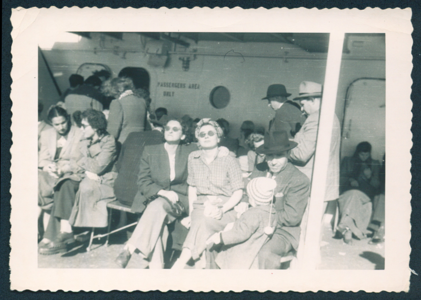 Immigrants to the United States enjoy the sunshine on the deck of the General Black.  Ada Abrahamer is sitting to the left of the wooden pillar wearing a scarf.