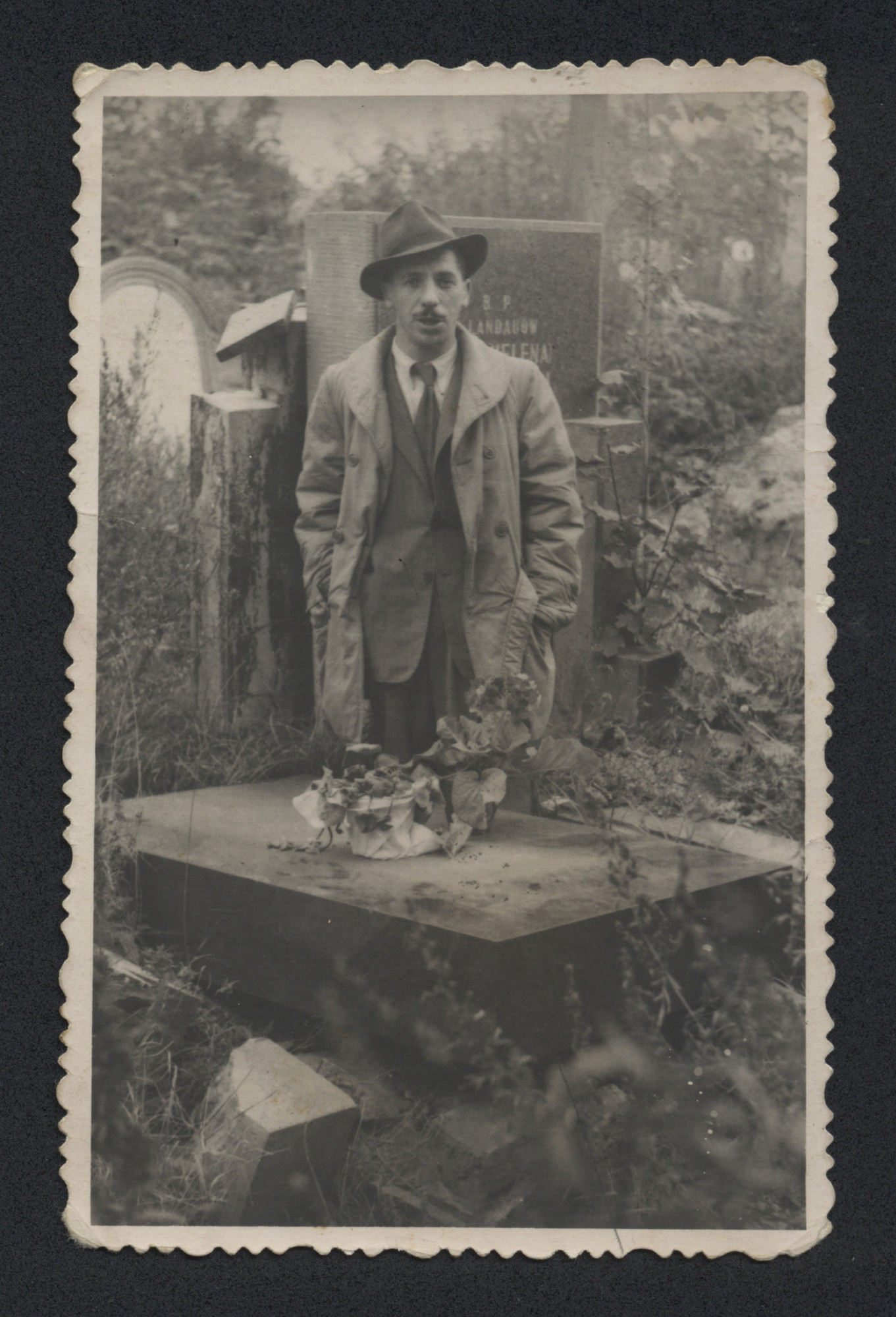 Lazar Ratafia stands next to the toppled gravemarker of his mother after the war.