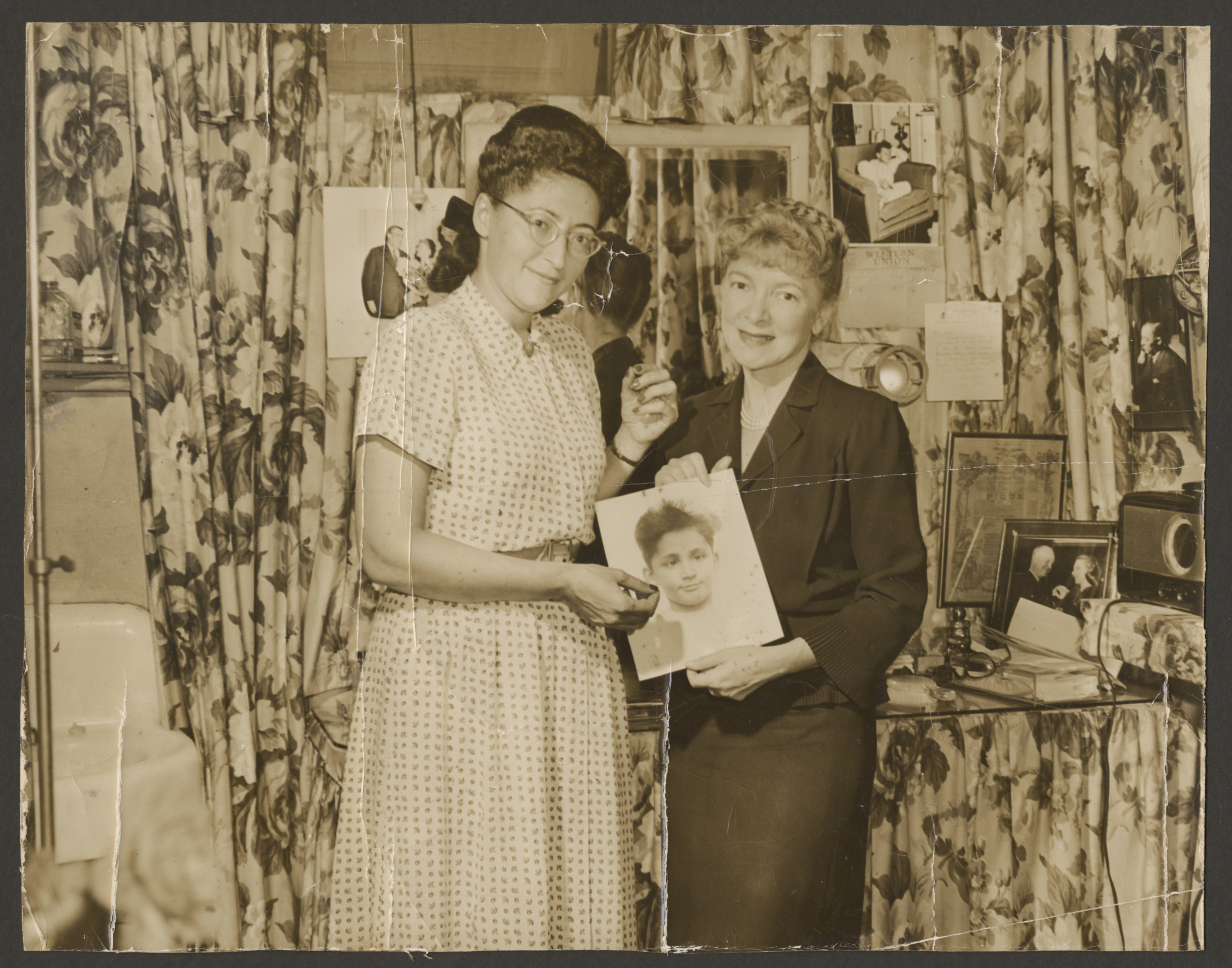 Ann Goldman poses with actress  Helen Hayes holding the photograph of a young European Jewish boy.  Helen Hayes agreed to adopt him through the organization, Save the Children.