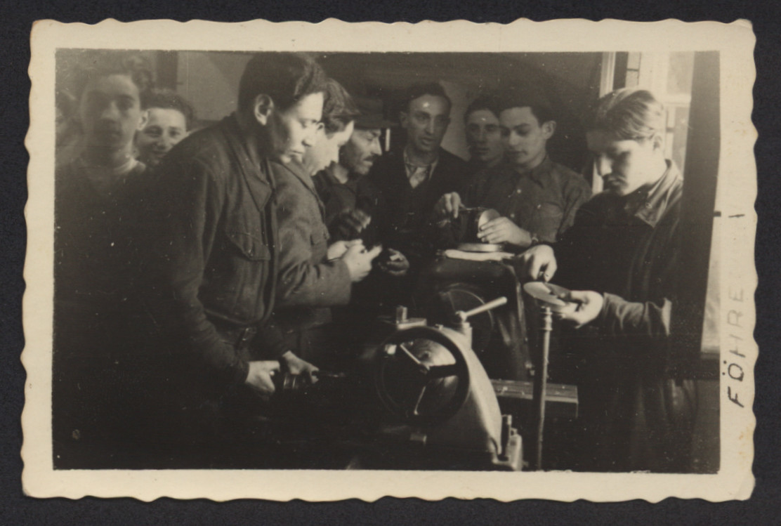 Young men learn mechanical skills in a vocational workshop in the Foehrenwald displaced persons camp.  Joseph Goetz is pictured on the left.  Pictured in the center, wearing a dark V-neck sweater, is Gad Goldman from Kalisz, Poland.