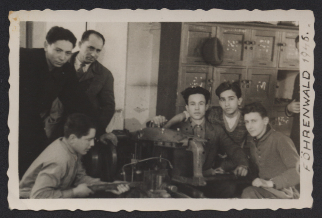 Young men learn mechanical skills in a vocational workshop in the Foehrenwald displaced persons camp.  Joseph Goetz is pictured on the left.