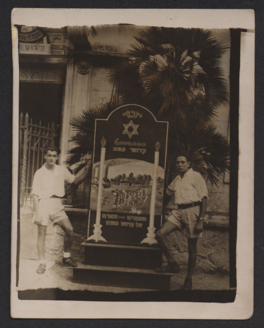 Two young men pose on either side of a memorial to Holocaust survivors [probably in Italy].  Joseph Goetz is standing on the right.