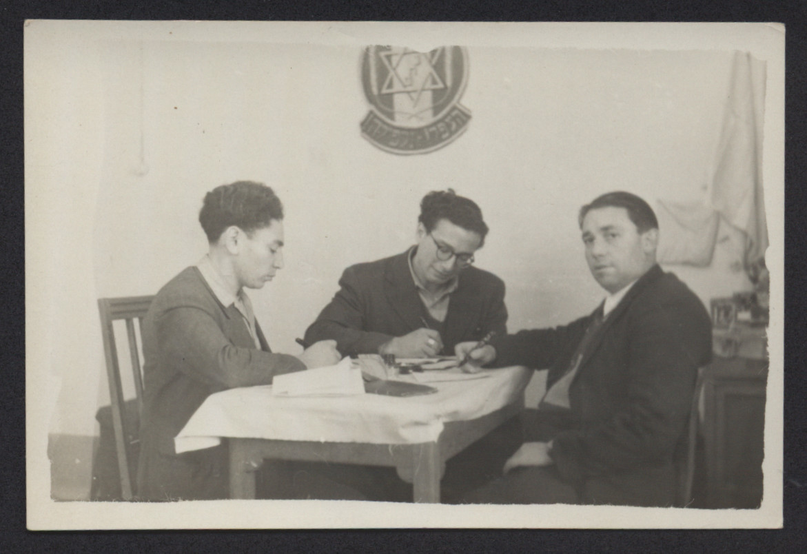 Three men work in an office of an unidentified displaced camp under a Zionist shield.  Joseph Goetz is pictured on the left.