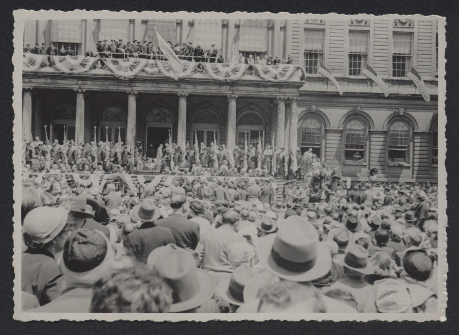 A large crowd gathers outside a building [perhaps in Italy] decorated with American and Israeli flags.  [It is possible the celebration was either of  the Declaration of Israeli Independence or of the Partition Plan.]