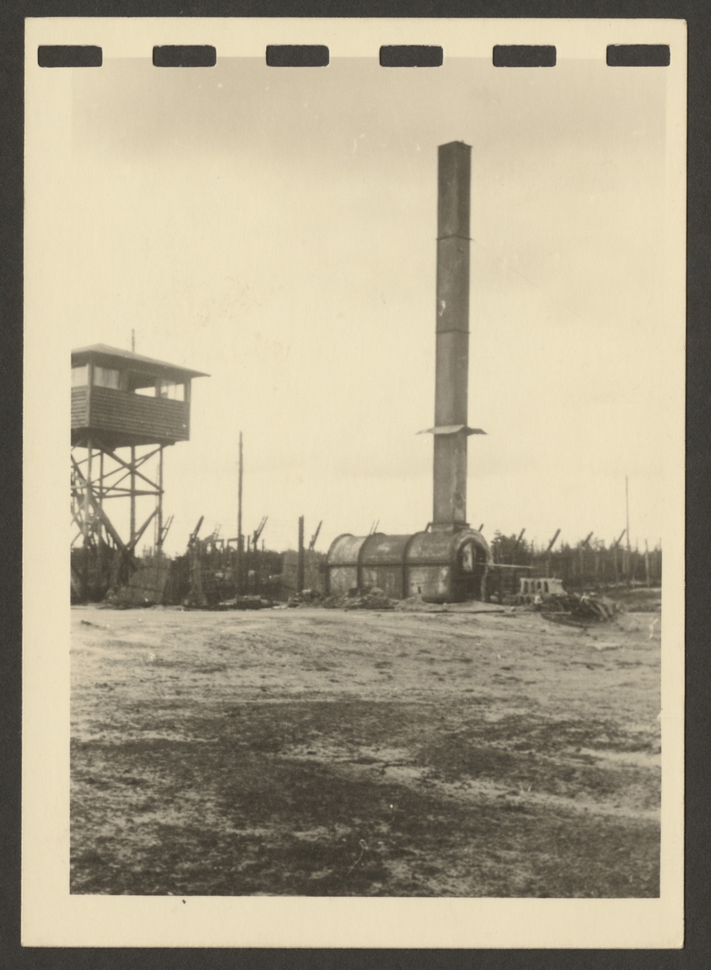 One page from a small photograph booklet containing images of Bergen-Belsen shortly after liberation.  Pictured is the crematorium, next to a watch tower.