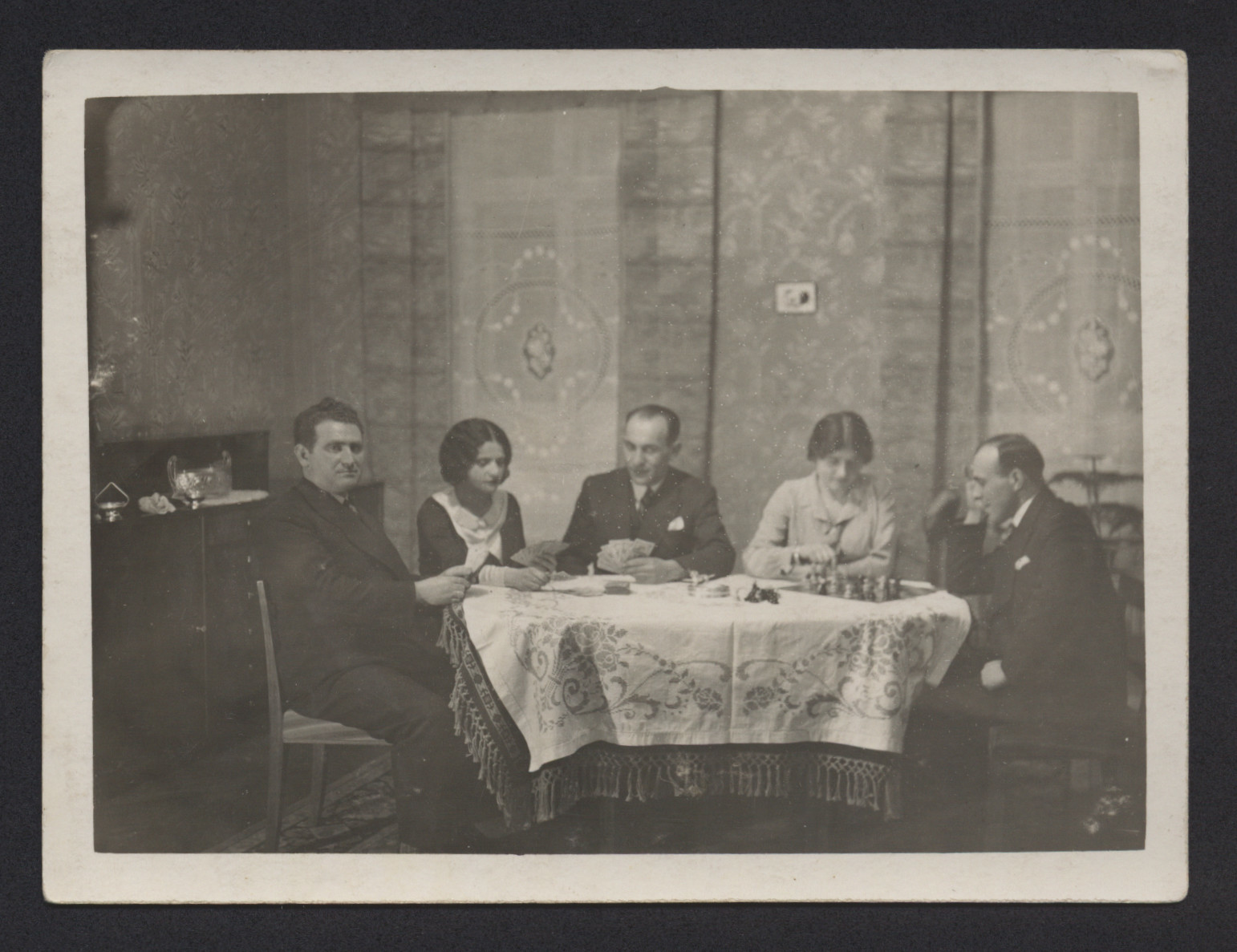 Juda and Schifra Tepper entertain guests in their apartment in Vienna.  Juda is pictured on the far left; Schifra is pictured  on the right, playing chess.