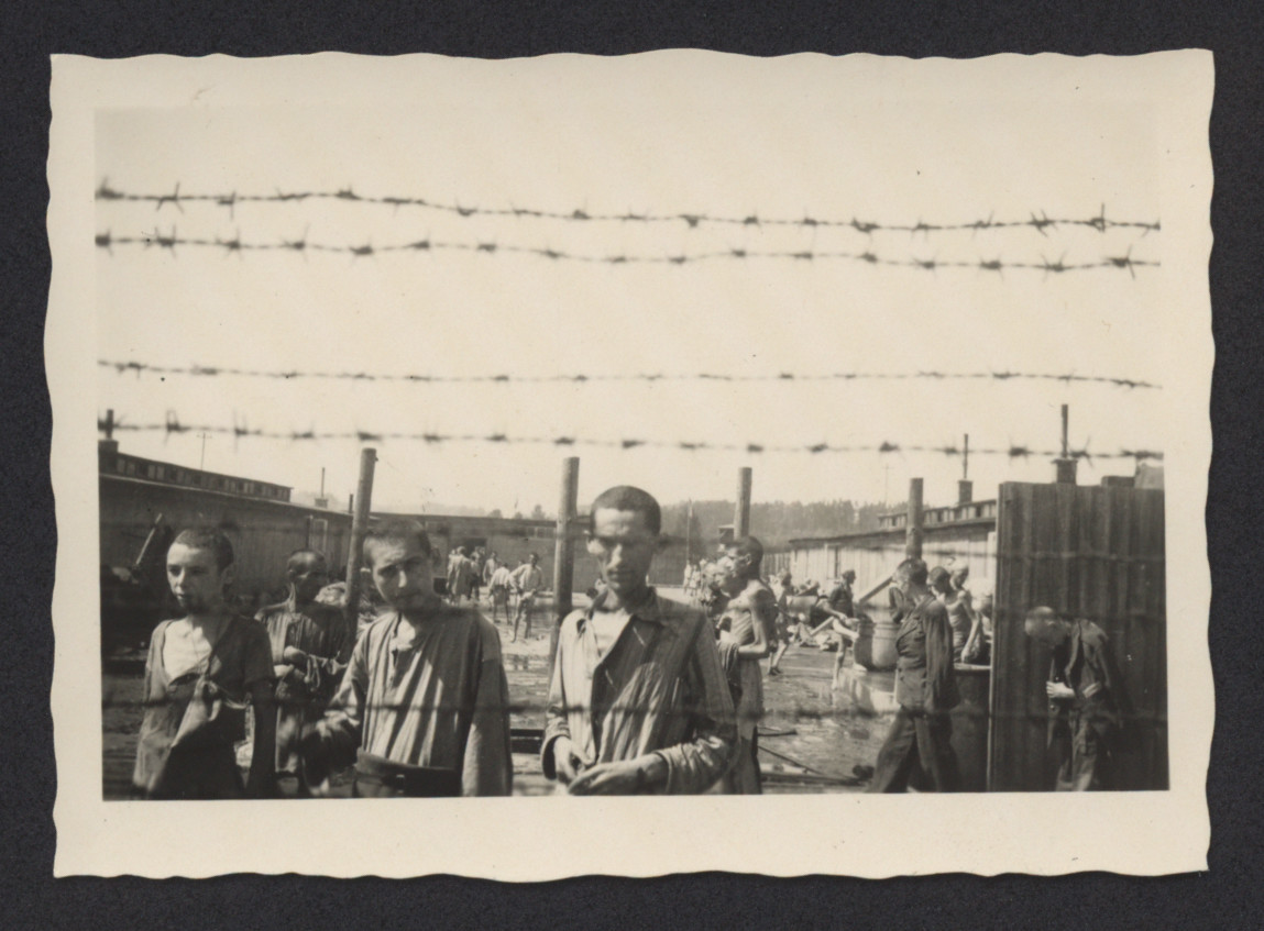 Survivors of Mauthausen are photographed through barbed wire.  This photograph is one of seven taken by Dr. Milton Silver's encounters at the Mauthausen concentration camp. Silver served with the 11th Armored Division during World War II, and on  May 5, 1945 he was among those troops who liberated the camp. Dr. Silver later returned with those American servicemen who entered the camp as part of a medical detail.