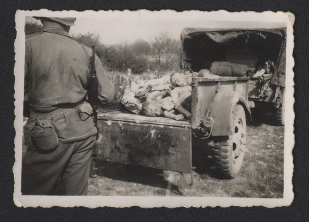 "An American soldier views corpses loaded onto a truck at Ohrdruf.  The original inscription reads, ""Murdered slaves about to get a decent burial.  Ohrdruf, Germany."""