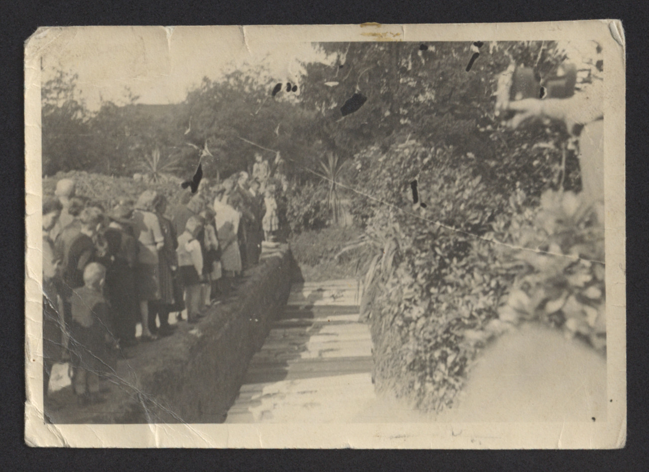 German civilians file past the open grave of concentration camp victims in Landsberg, prior to reburial.