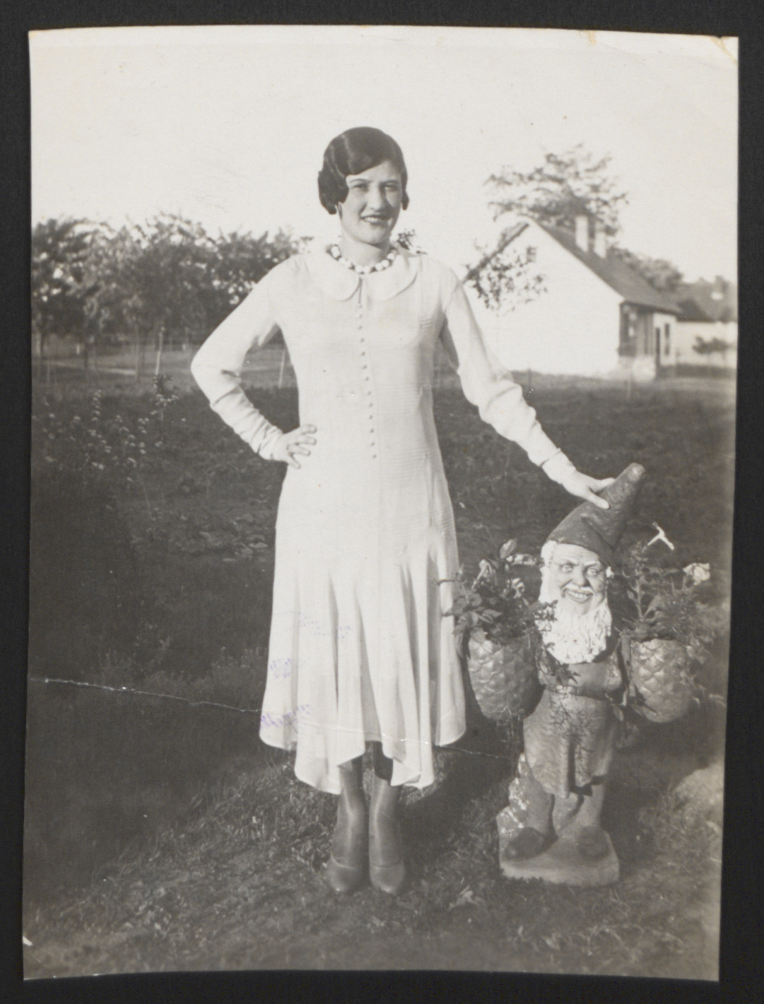 Lilly Roth poses next to a garden gnome.