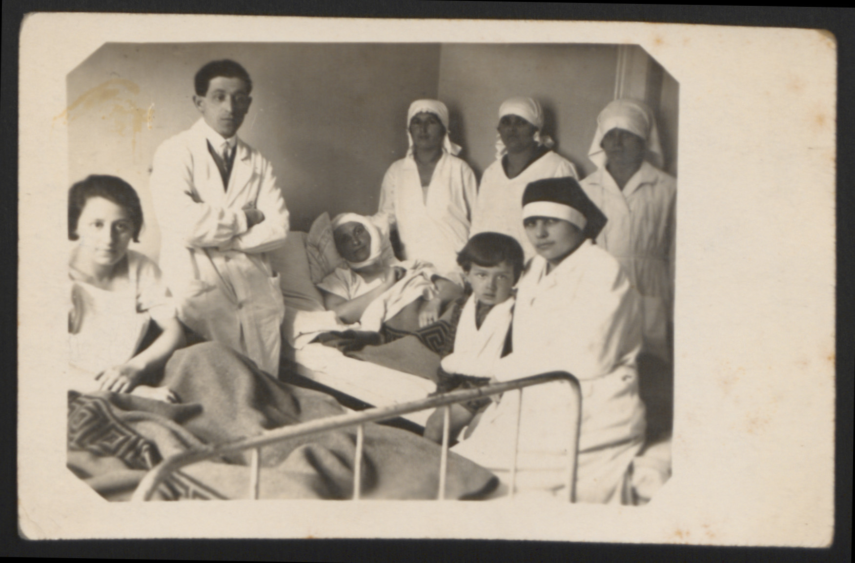 Dr. Ladislav Merei and a group of nurses gather around a patient in prewar Czechoslovakia (either Prague or Bratislava).