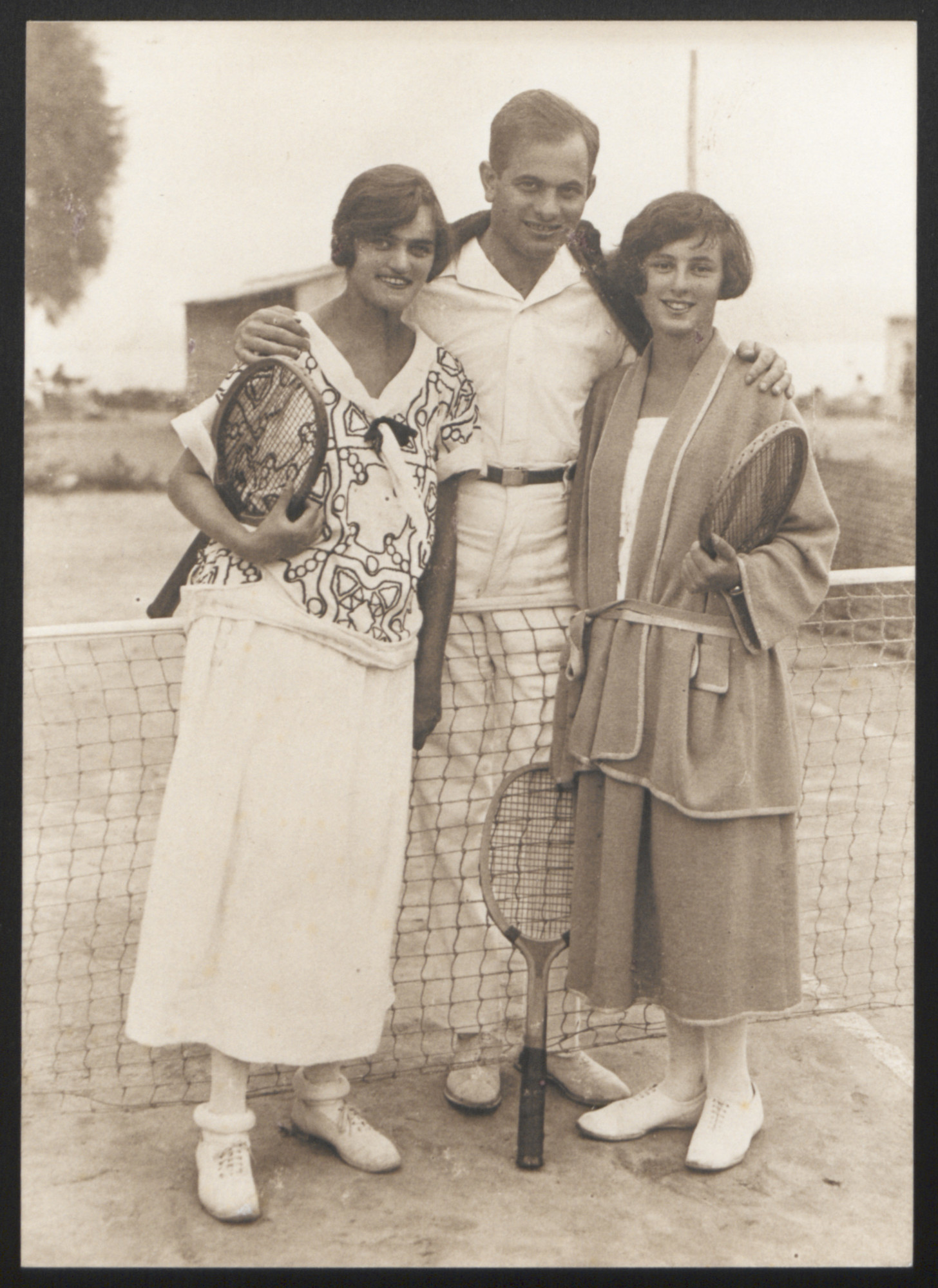 Ernestine (Ily) Munk, her brother Louis Munk, and his sister-in-law Macko Garay (nee Adler) pose together at a tennis court.