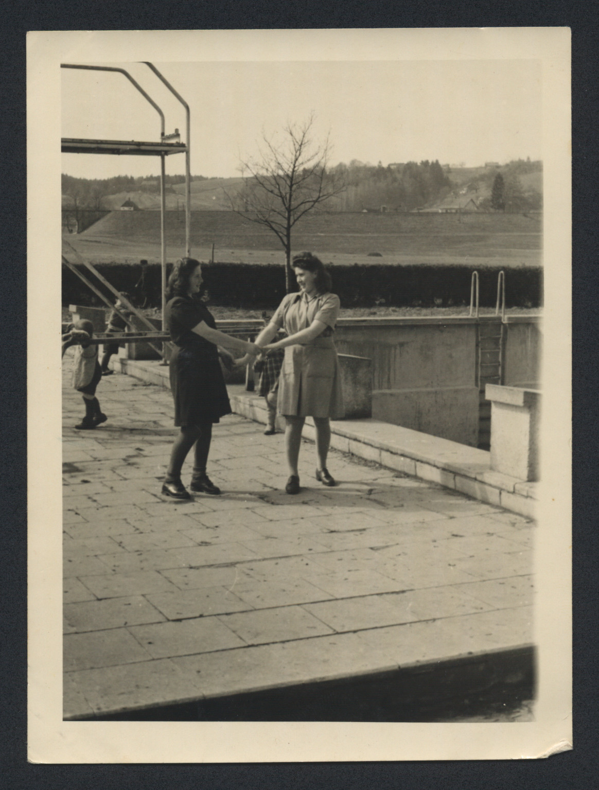 Lenke Gruenberg (left) and a friend hold hands next to the swimming pool in Deggendorf.