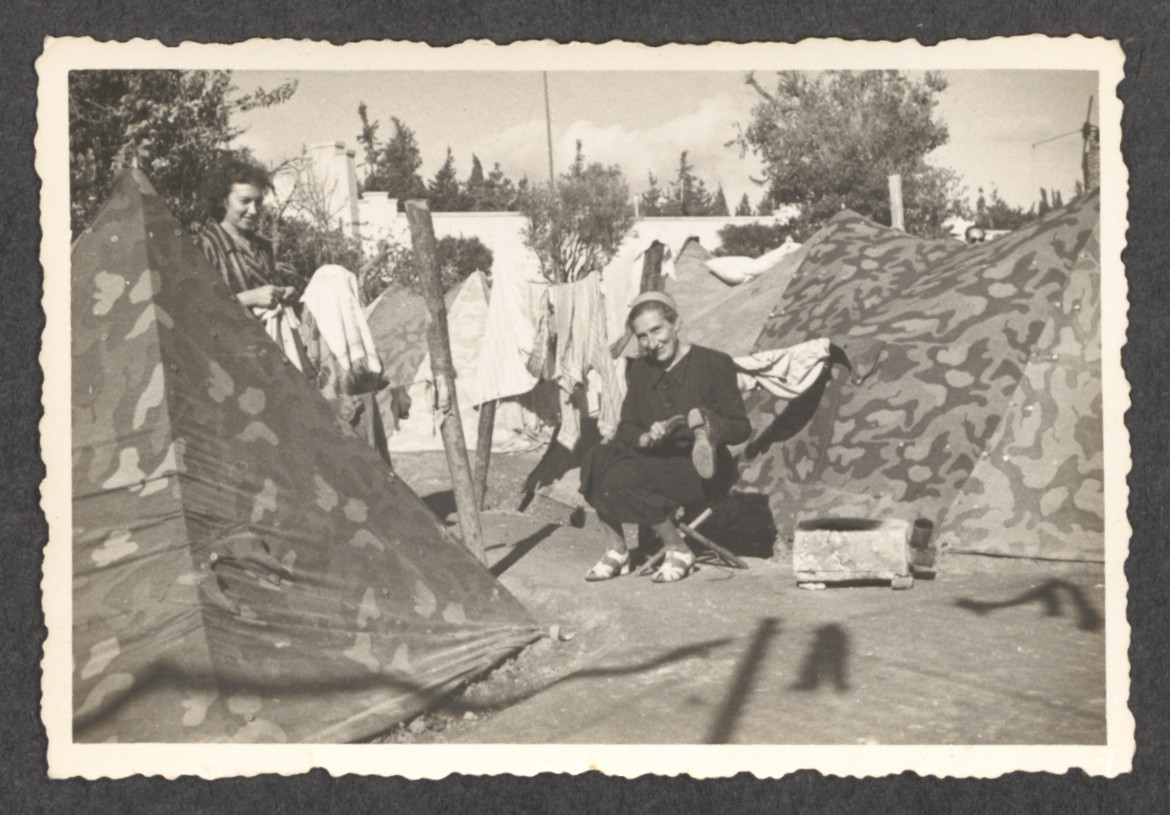 Jewish refugees from the shipwrecked Pentcho sit amid their tents in the soccer stadium on the island of Rhodes.  Pictured seated is Stefanie Fellner.