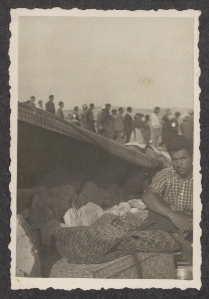A Jewish refugee from the shipwrecked Pentcho sits near a make-shift shelter, while in the background fellow refugees line up for provisions.