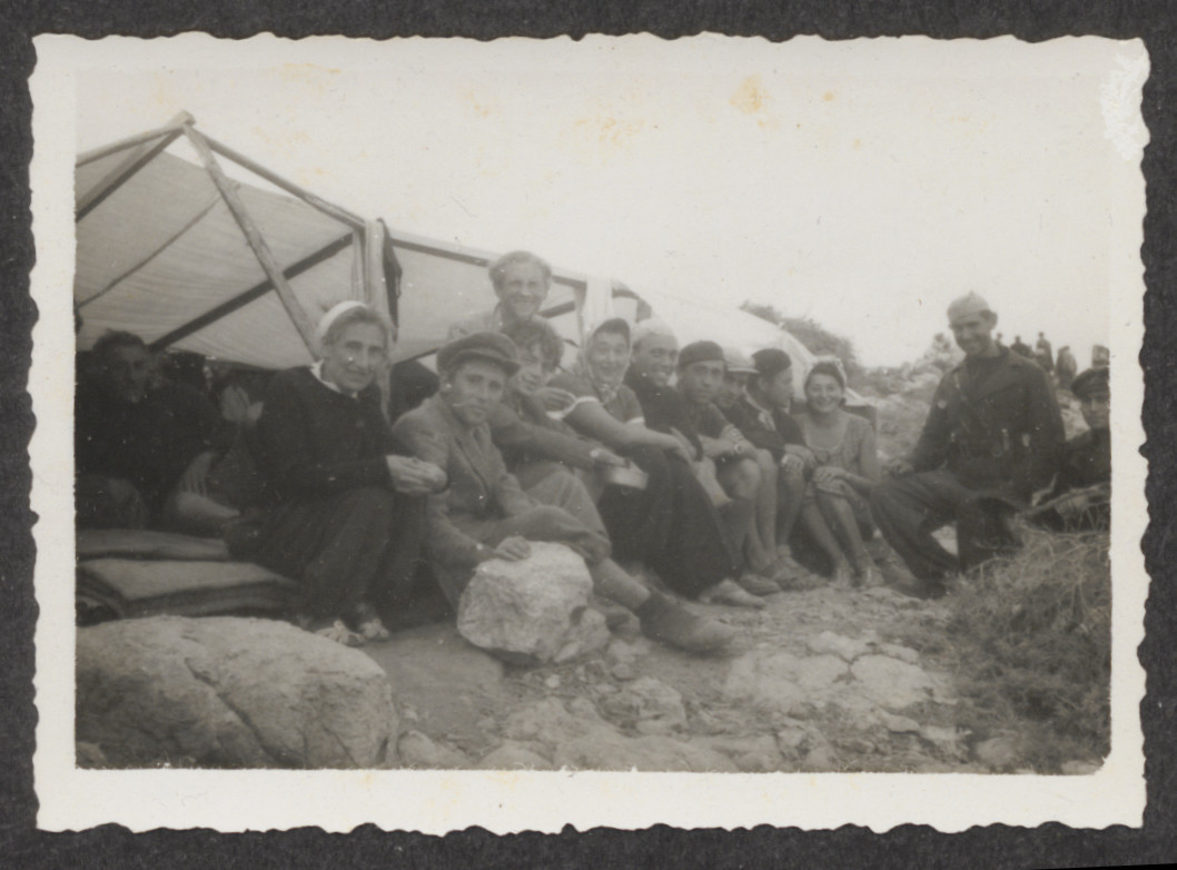 Jewish refugees from the shipwrecked Pentcho sitting next to a make-shift shelter, [possibly with their Italian rescuers], on the island of Kamilonissi.  Pictured on the left is Stefanie Fellner.