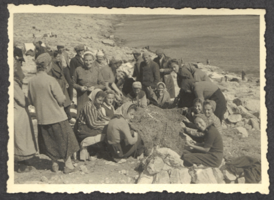 "Jewish refugee women who were passengers on the the Pentcho work together  [possibly on some netting], while shipwrecked on the the island of Kamilonissi.   Among those pictured is Stefanie Fellner (standing on the left, wearing a white head scarf).  The inscription on the back reads, ""Deserted Island."""