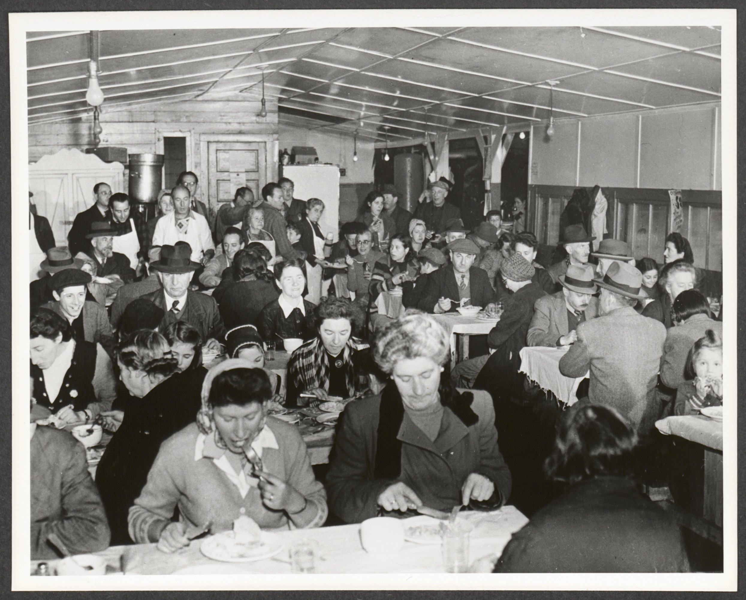 Jewish refugees eat a meal in a dining room at Fort Ontario.   Beila Deutscher is pictured in center of frame.