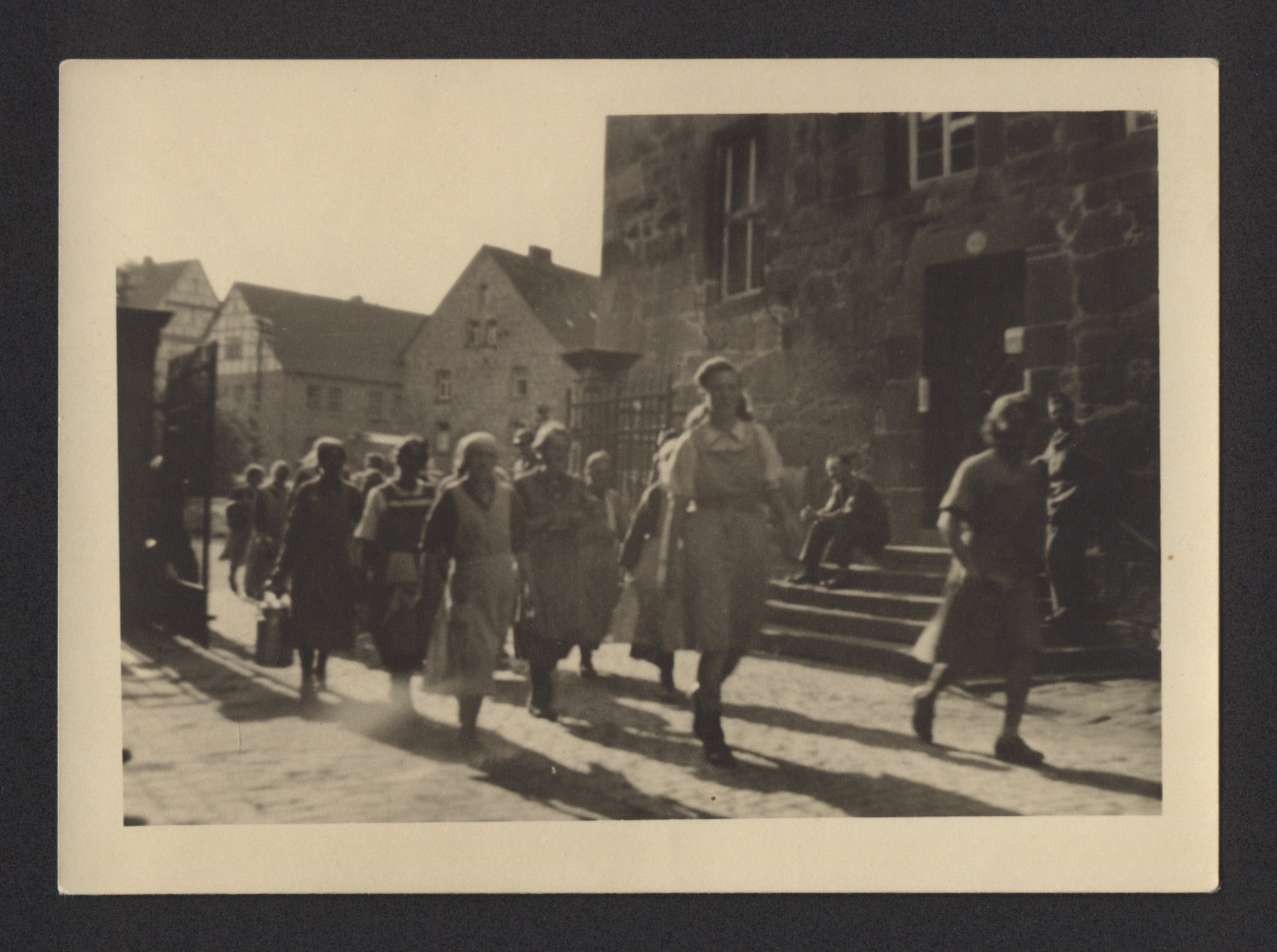 "Women enter the Merxhausen sanitorium gates.  The inscription on the back of the photograph reads, ""Women coming in from work.  Merxhausen."""