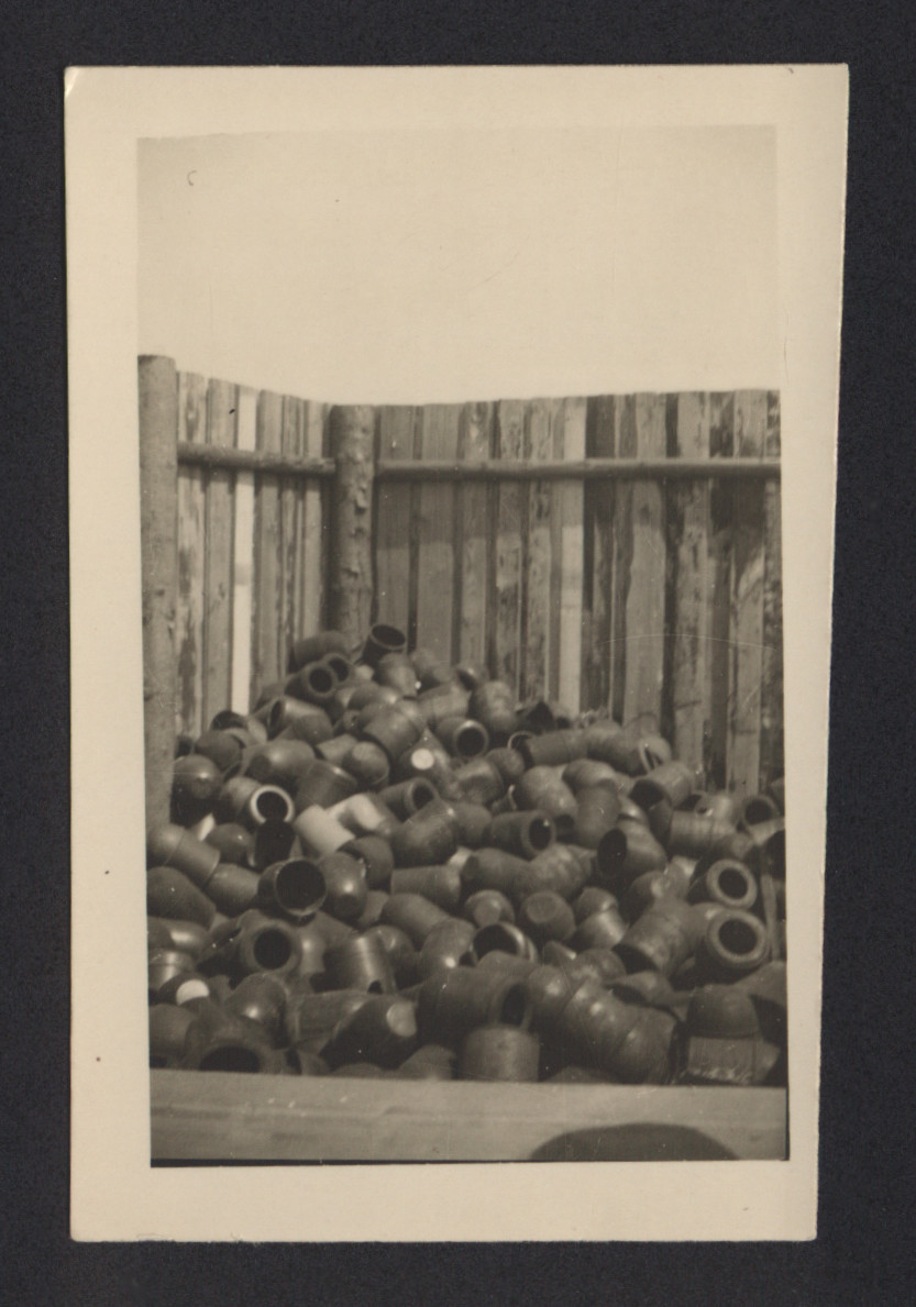 "Funerary urns stacked against a wooden fence at Buchenwald.  The urns were supplied by Topf & Sons company of Erfurt, and used by the Nazis to keep up a pretense of proper handling of the remains of victims.  The inscription on the back of the photograph reads, ""Jars for Ashes Buchenwald.""  Source:  https://www.buchenwald.de/en/1268/"