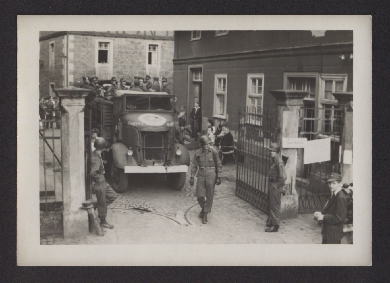 """Prisoners [?] in the back of a truck leave the Merxhausen sanitorium with the assistance of American soldiers.    The inscription on the back of the photograph reads, """"Prisoners going out Merxhausen."""""""