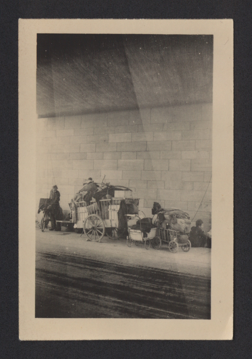 "Postwar refugees hauling their possessions in carts travel along the Autobahn to Weimar.  The pencil inscription on the back of the photograph reads, ""Refugees under viaduct during rain along autobahn to Weimar."""