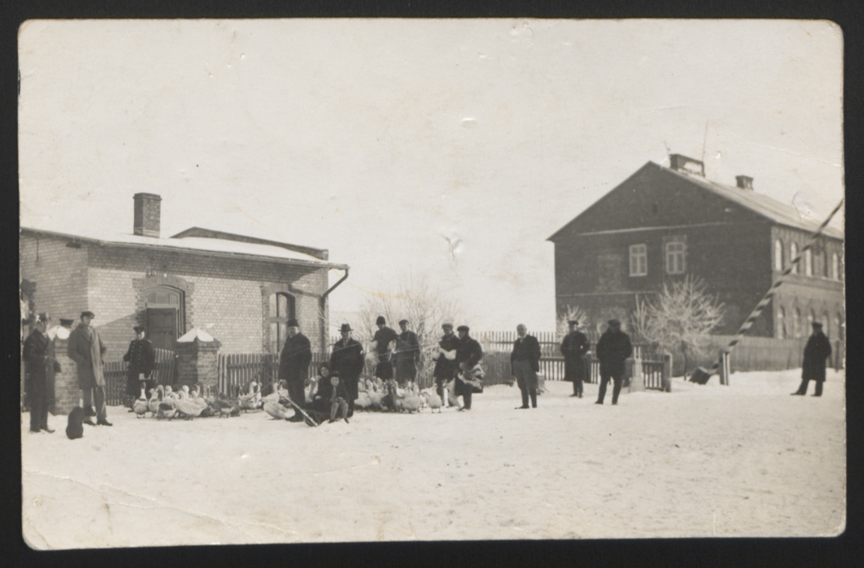 """A group of people  with geese gather in front of a building.  The inscription on the back of the photograph reads, """"1930."""""""