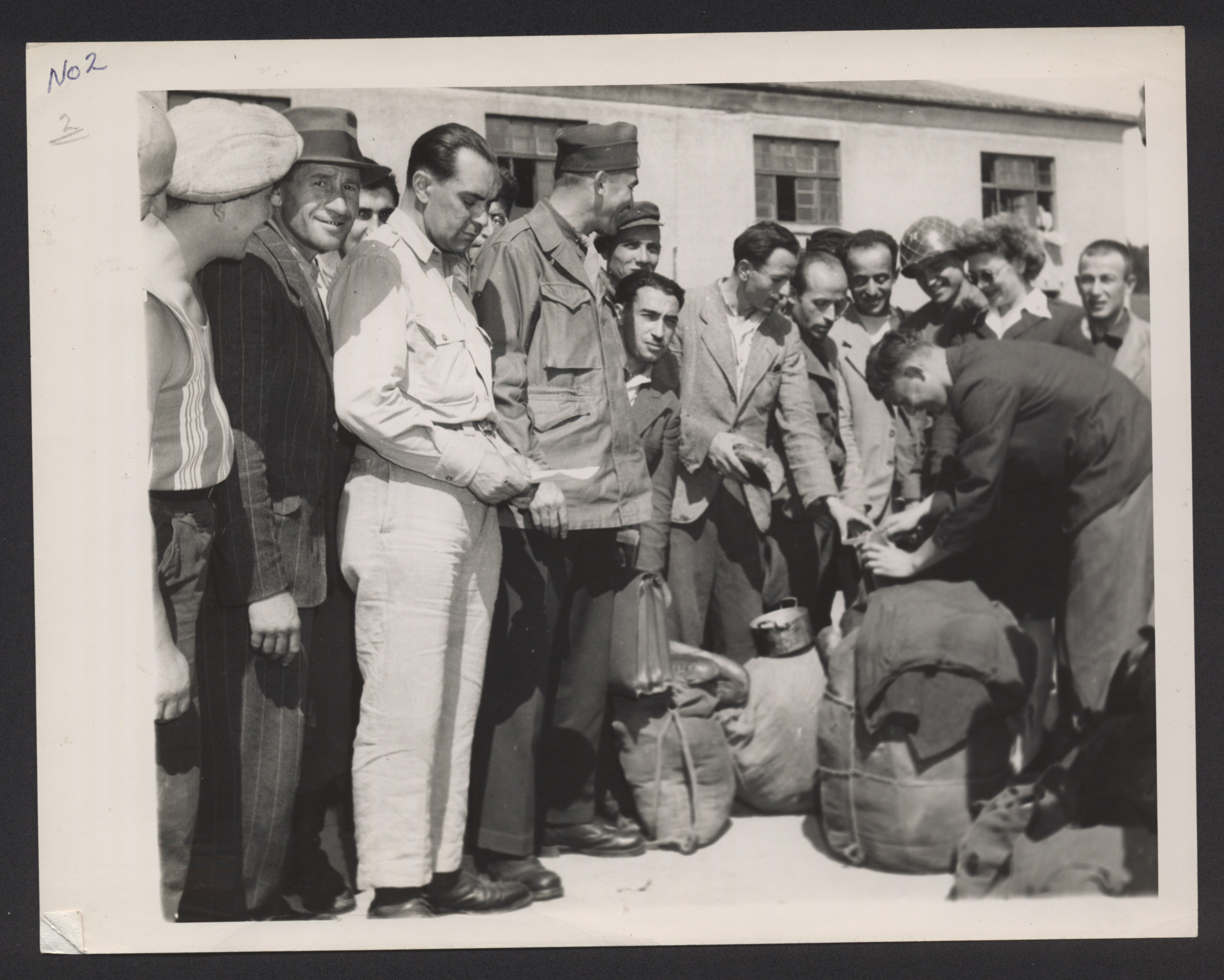 American soldiers pose with Jewish DPs with packed bundles who are either arriving or leaving a DP camp [probably Bad Gastein].