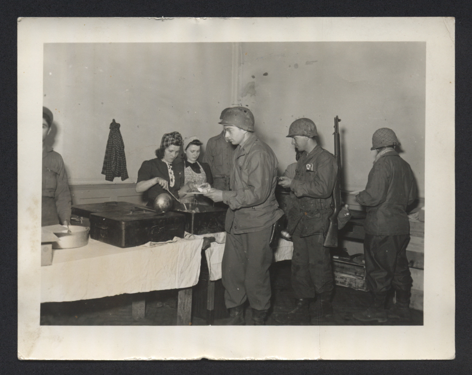 Women serve food to American GIs [perhaps in the Bad Gastein displaced persons camp.]