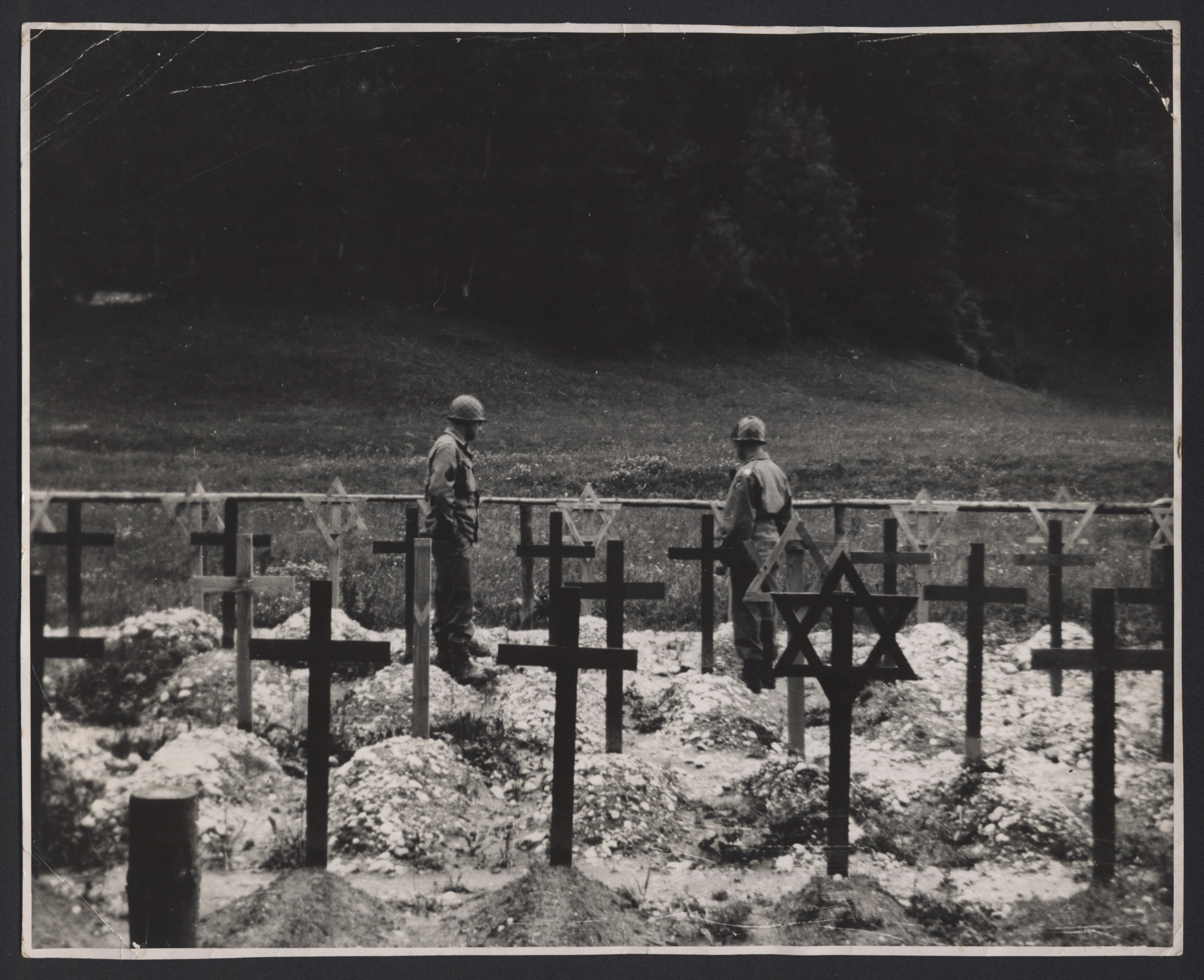 Two American soldiers walk in a cemetery of newly dug graves for both Jewish and Christian fallen comrades.