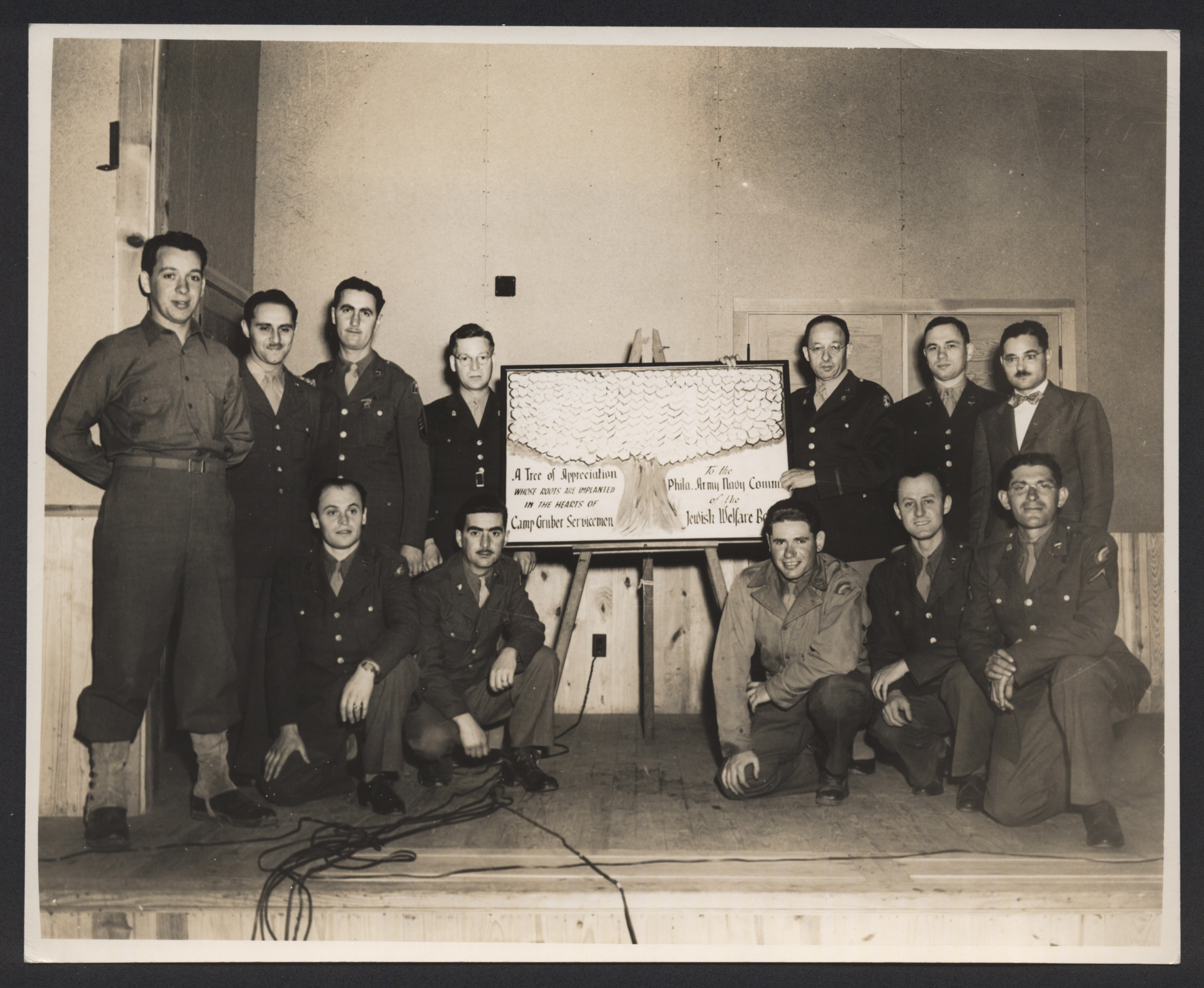 American Jewish servicemen pose around a  certificate of appreciation issued by the Jewish Welfare Board of Philadelphia.