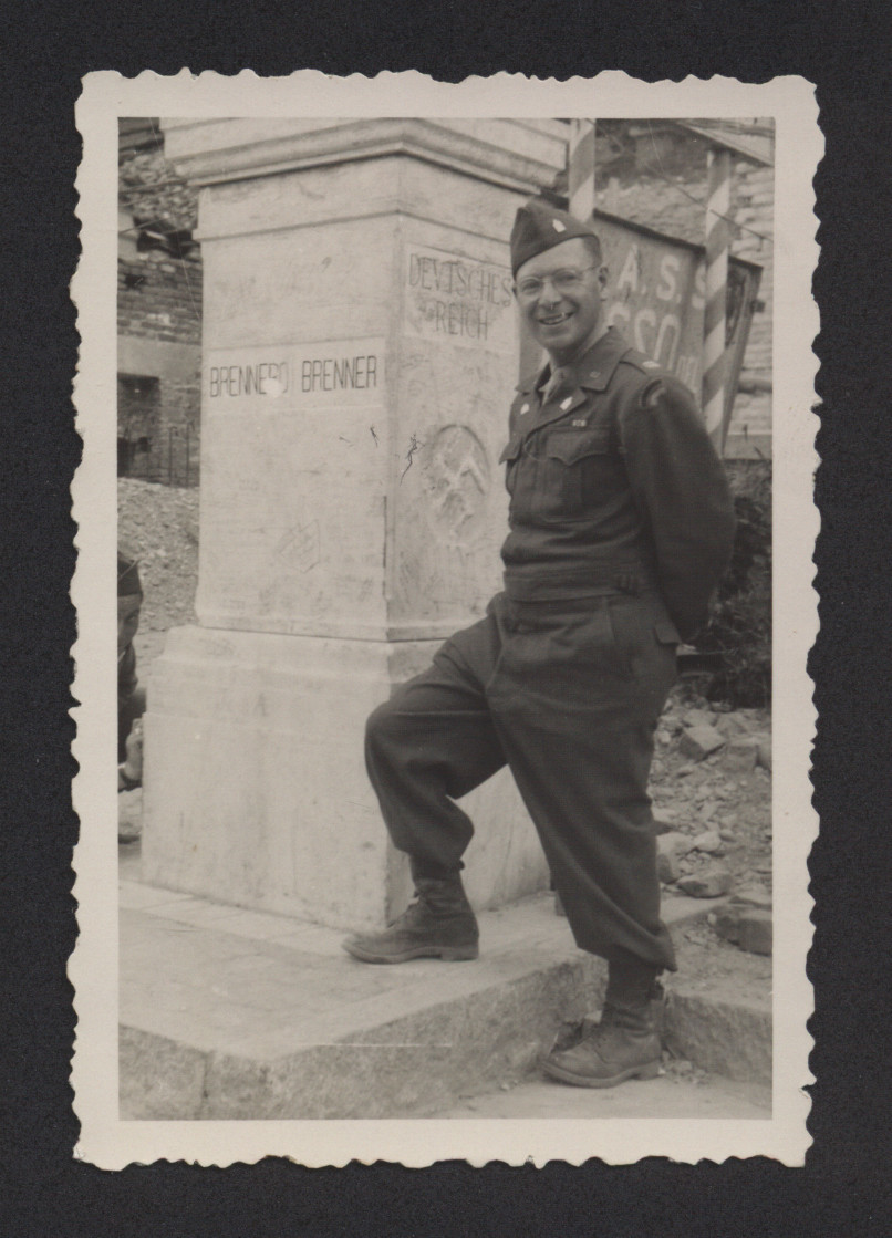 "Rabbi Eli Bohnen poses next to a Nazi pillar at the Brenner Pass.  The original caption reads: ""At the Brenner Pass.  Note partially erased Swastika."""