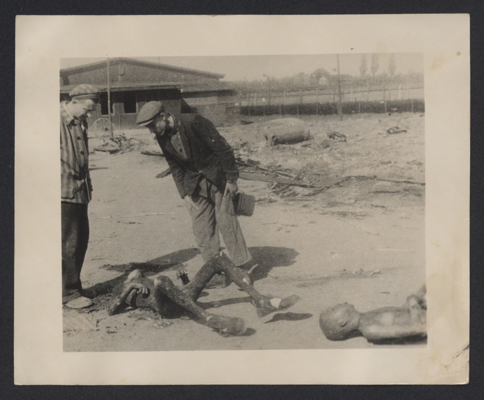Survivors view charred corpses at Leipzig-Thekla, a subcamp of Buchenwald.