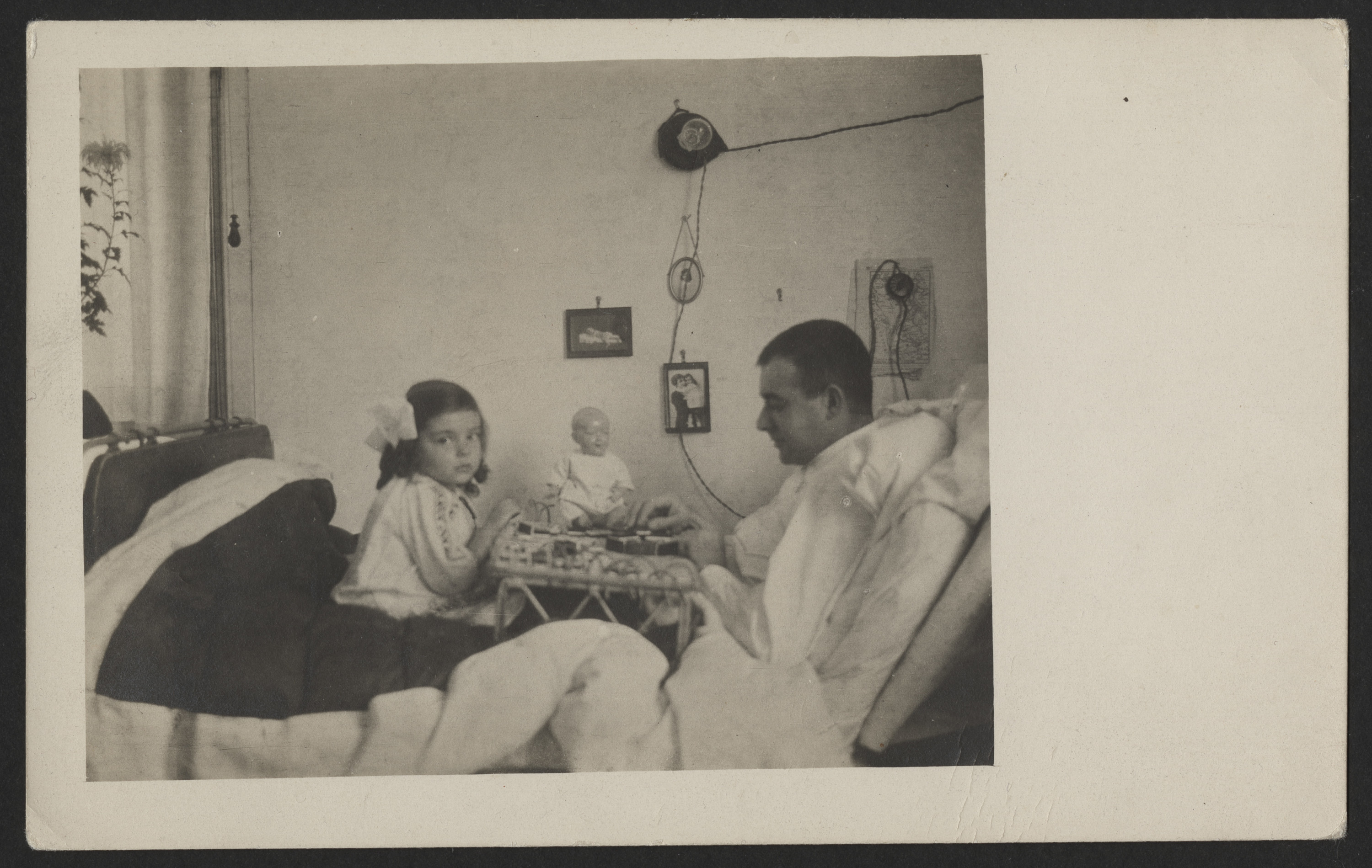 "Max Levi seated in a hospital bed, playing a game with his young daughter, Margot.  The inscription on the back (in German) reads, ""December 1915."""