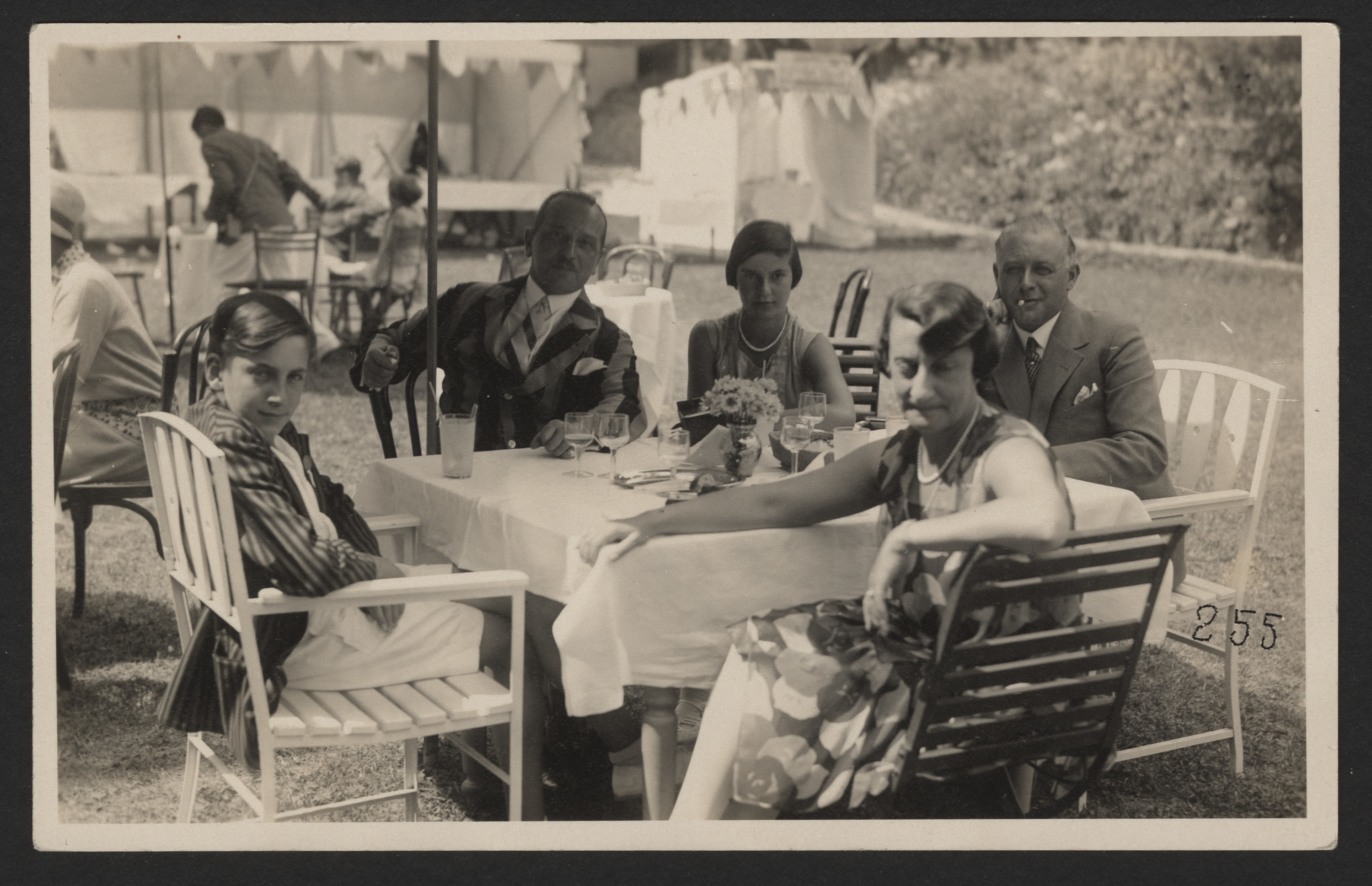 The Levi family sits around an outdoor dining table.   Among those pictured (left to right) are Walter, [unidentified], Margot, Nellie, and Max Levi.