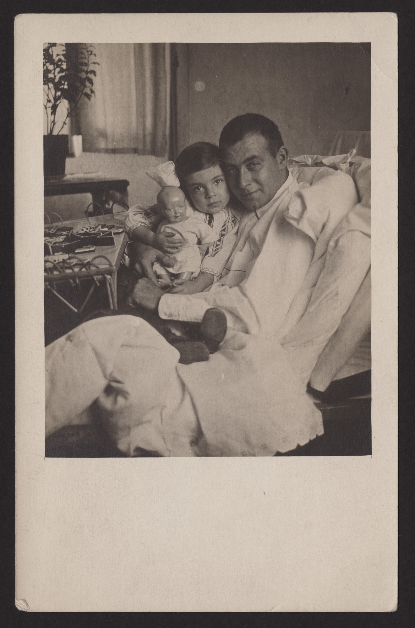 """Max Levi in a hospital bed, hugs his daughter Margot seated on his lap.  The inscription on the back of the photograph (translated from German) reads, """"Christmas 1915, hospital."""""""