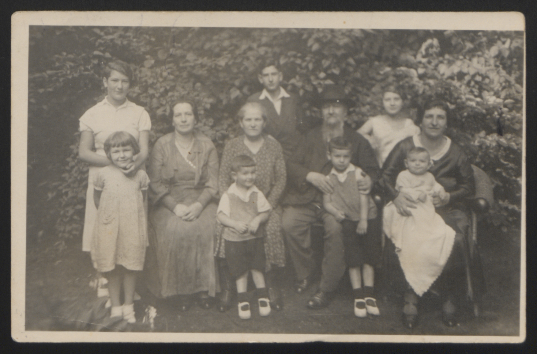 Portrait of the Hausner family of Hamburg, Germany.   Pictured are Gershon and Rivka Hausner (seated in the center), their son Natan Hausner (back row, center), their daughter Sara (Hausner) Selzer (second from the left), her daughters Cilli and Gila (far left),  Rachel (Hausner) (far right), and her sons Eli, Karl Heinz, and Wolfgang (front, left to right).
