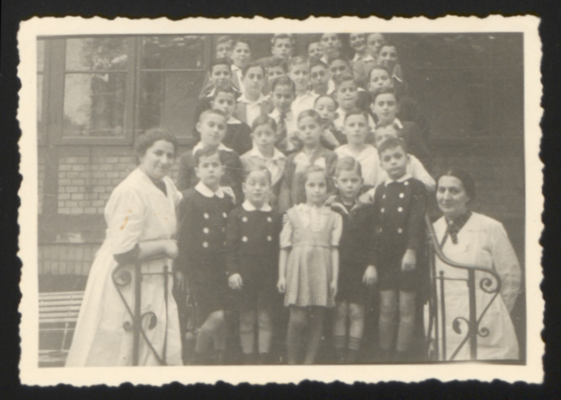 Group portrait of  children and two female staff members standing on the steps of the orphanage run by the Jewish community in Hamburg, Germany.   Among those pictured is caretaker Minna Gottschalk (left).