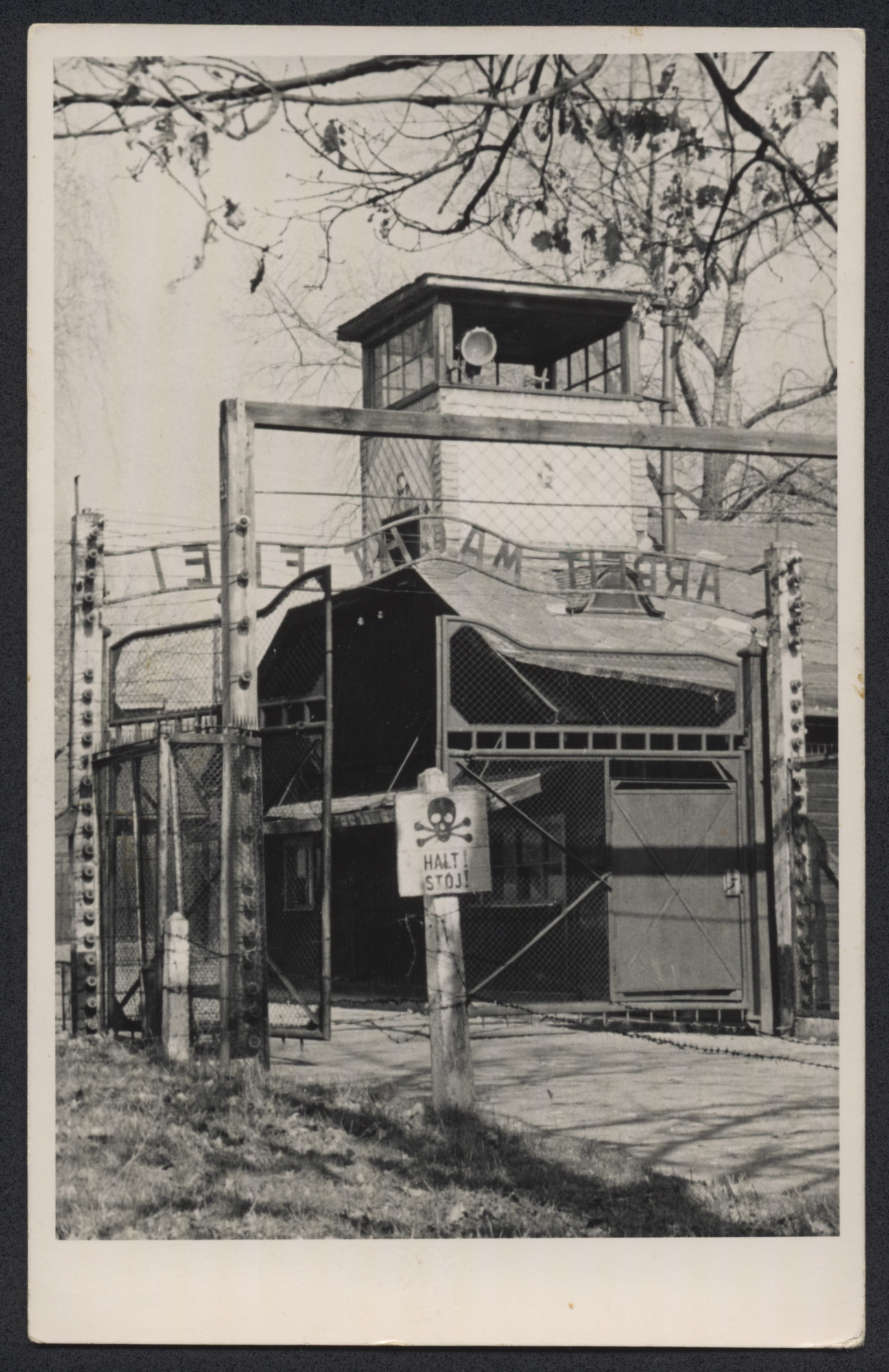 """Postwar photograph of an exit from the main Auschwitz camp, showing a warning sign, guard tower, and """"Arbeit Macht Frei"""" over the gate."""